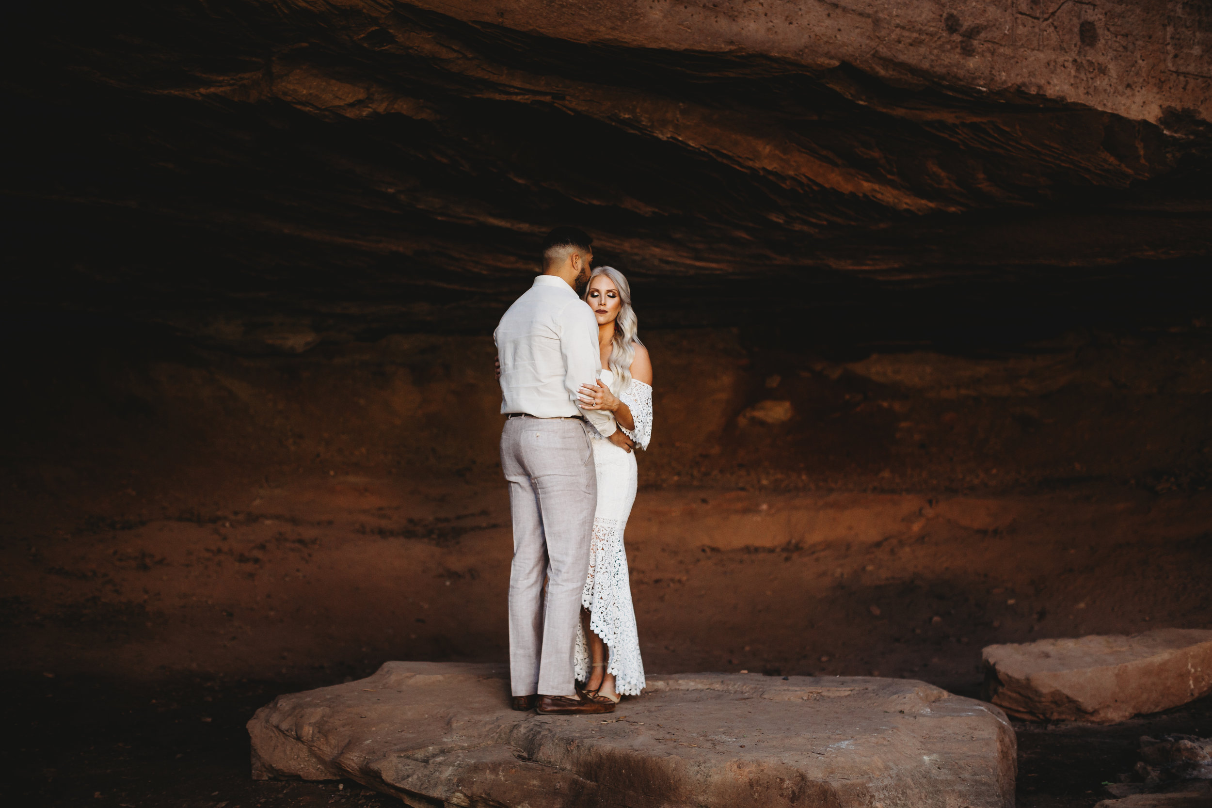 Standing together under red sandstone in white neutral colors #engagementphotos #riverfalls #engaged #personality #amarillotexas #engagementphotographer #lifestylephotos #amarillophotographer #locationchoice #texasengagementphotos #engagment #tealawardphotography #wildliferefuge