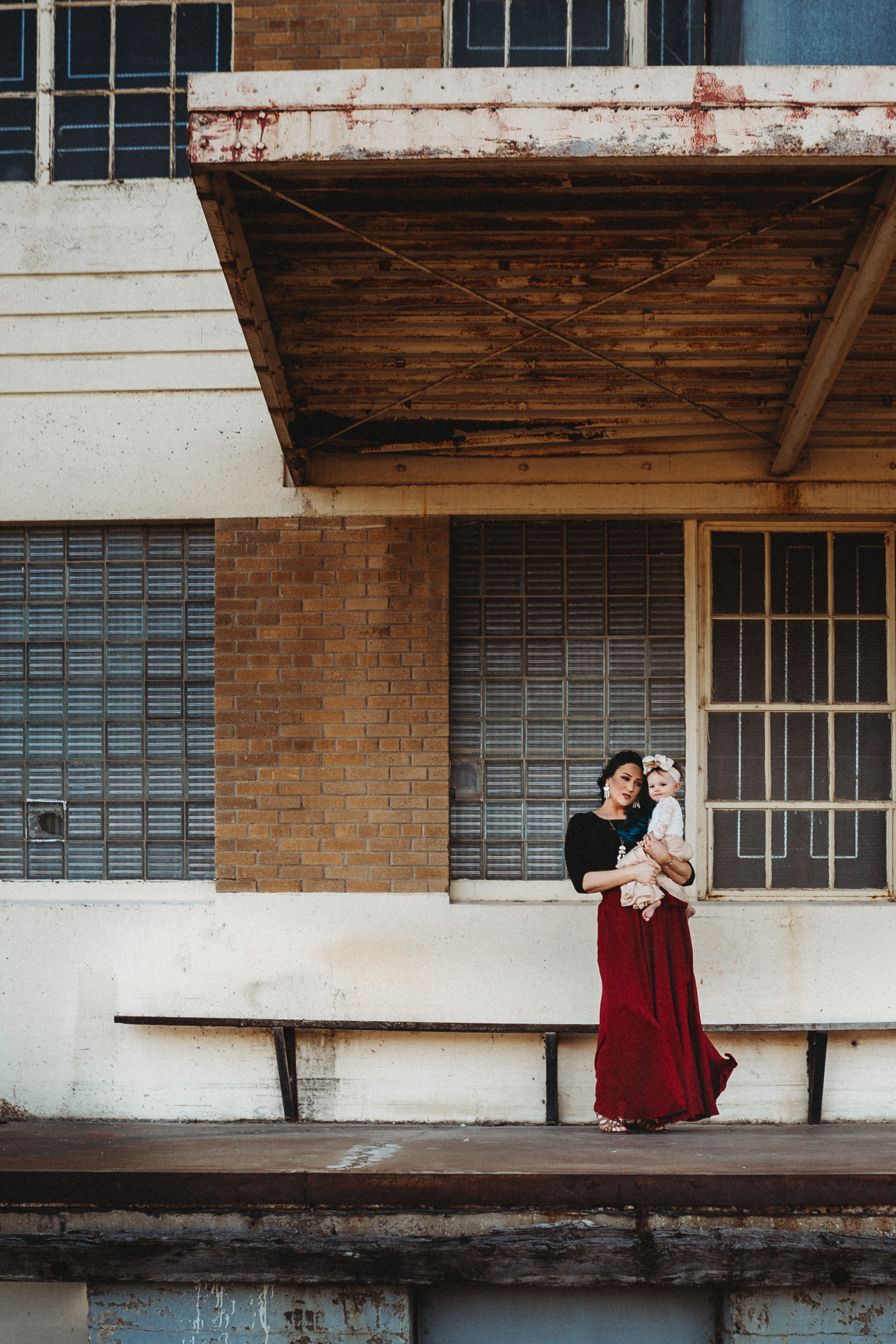 Mom and baby together with a bond that is unbreakable, ruby red dress to stand out in front of neutral downtown #rubyred #familyphotos #downtown #hairstyle #personality #amarillotexas #familyphotographer #lifestylephotos #amarillophotographer #locationchoice #texasfamilyphotos #familyofthree