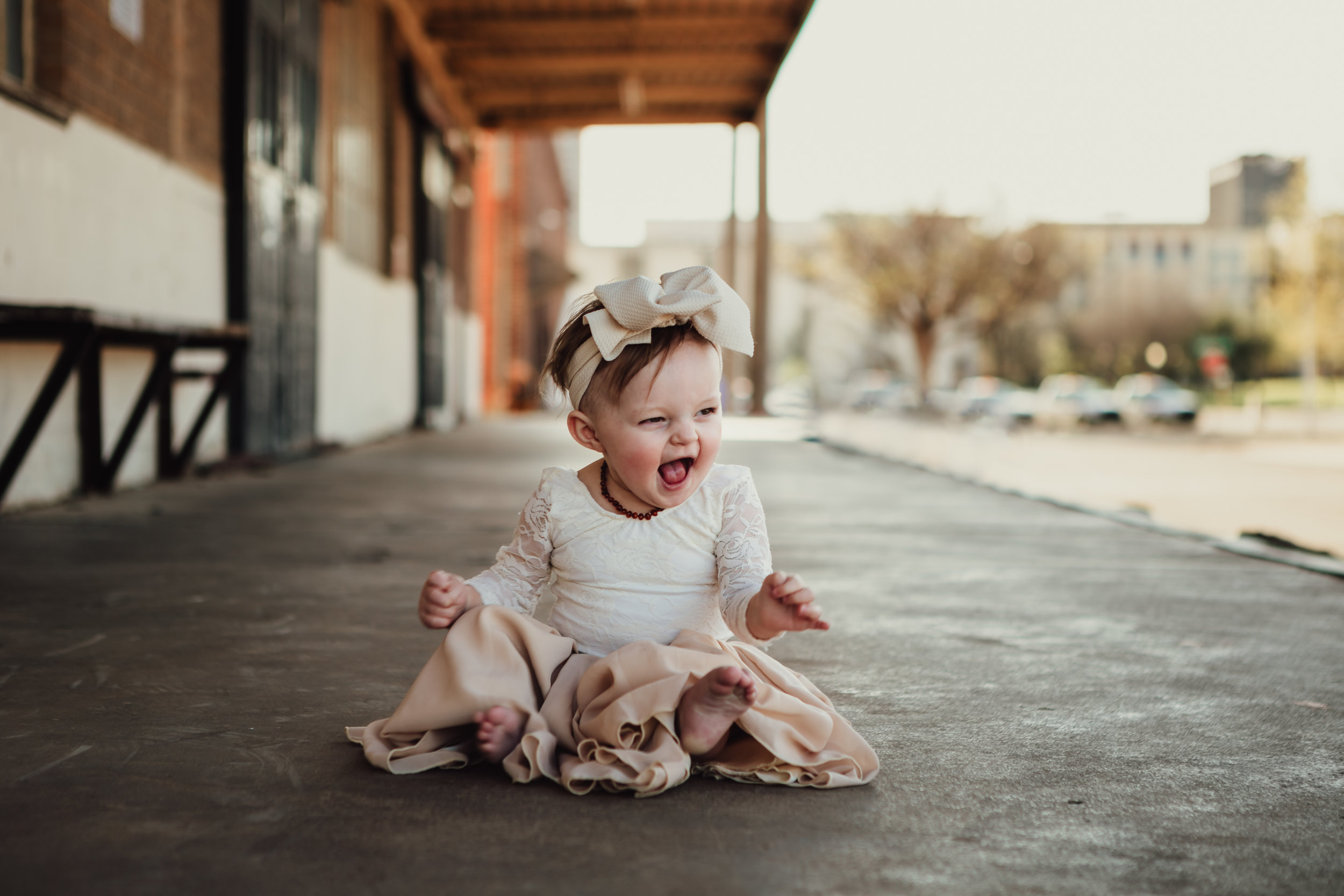 Laugh of a little one captured in neutral wardrobe and large bow #rubyred #familyphotos #downtown #hairstyle #personality #amarillotexas #familyphotographer #lifestylephotos #amarillophotographer #locationchoice #texasfamilyphotos #familyofthree
