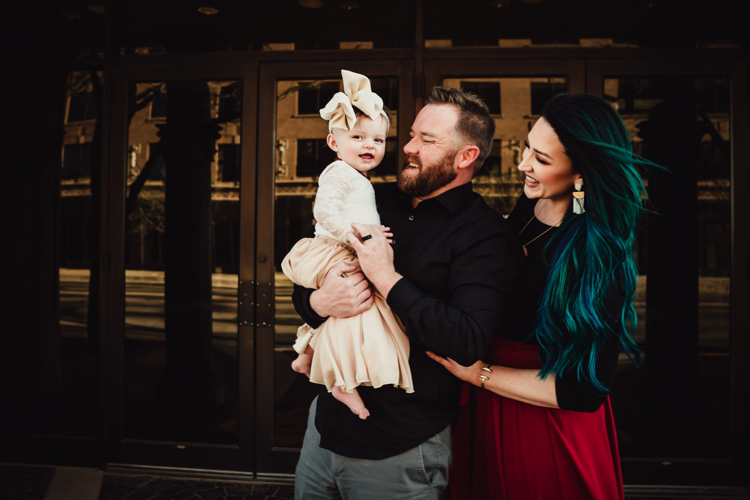 Downtown light and gold mirror doors behind family gazing at little one in awe of her beauty #rubyred #familyphotos #downtown #hairstyle #personality #amarillotexas #familyphotographer #lifestylephotos #amarillophotographer #locationchoice #texasfamilyphotos #familyofthree