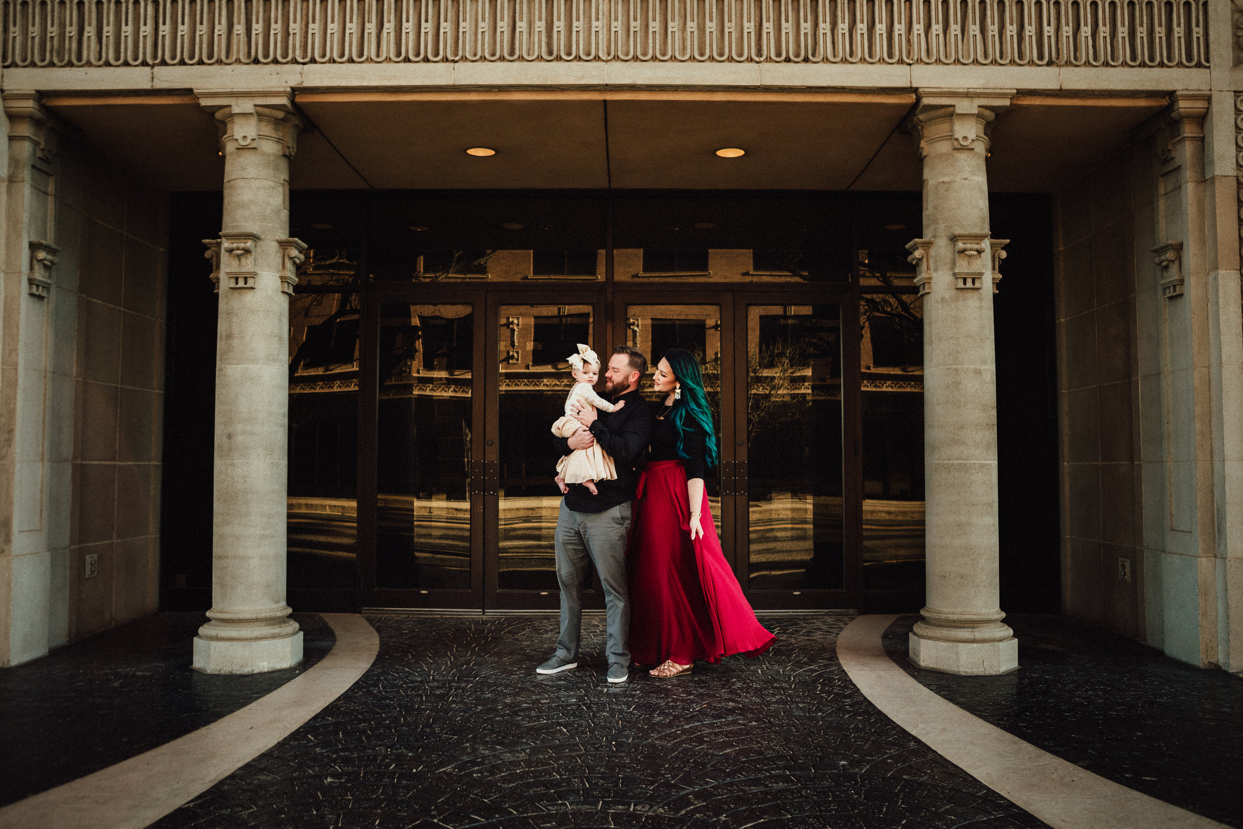 Distance photo of family of three in front of downtown building ruby red dress and neutral dress for the little one #rubyred #familyphotos #downtown #hairstyle #personality #amarillotexas #familyphotographer #lifestylephotos #amarillophotographer #locationchoice #texasfamilyphotos #familyofthree