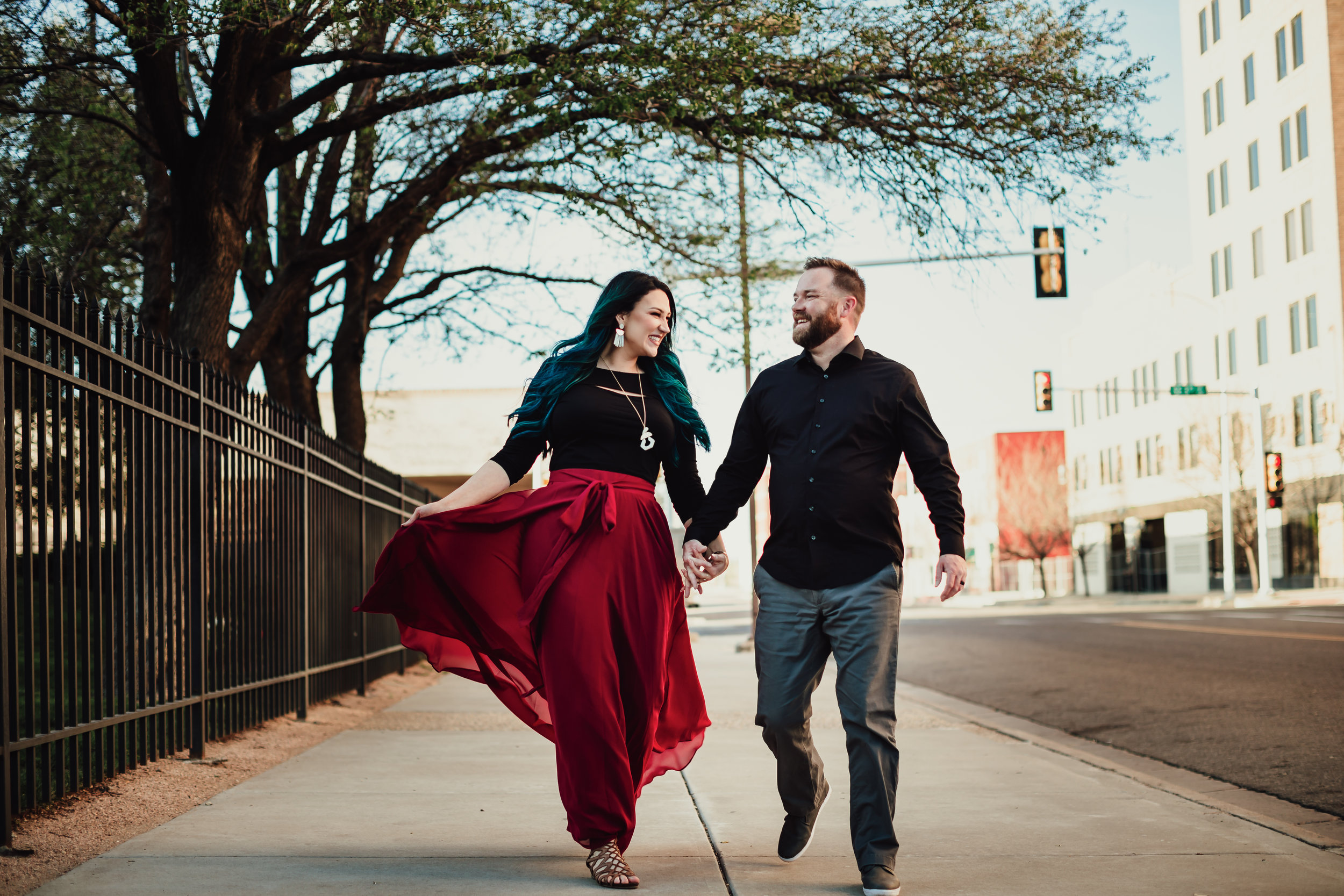 Couple photo walking adjacent to fence in downtown Amarillo together #rubyred #familyphotos #downtown #hairstyle #personality #amarillotexas #familyphotographer #lifestylephotos #amarillophotographer #locationchoice #texasfamilyphotos #familyofthree