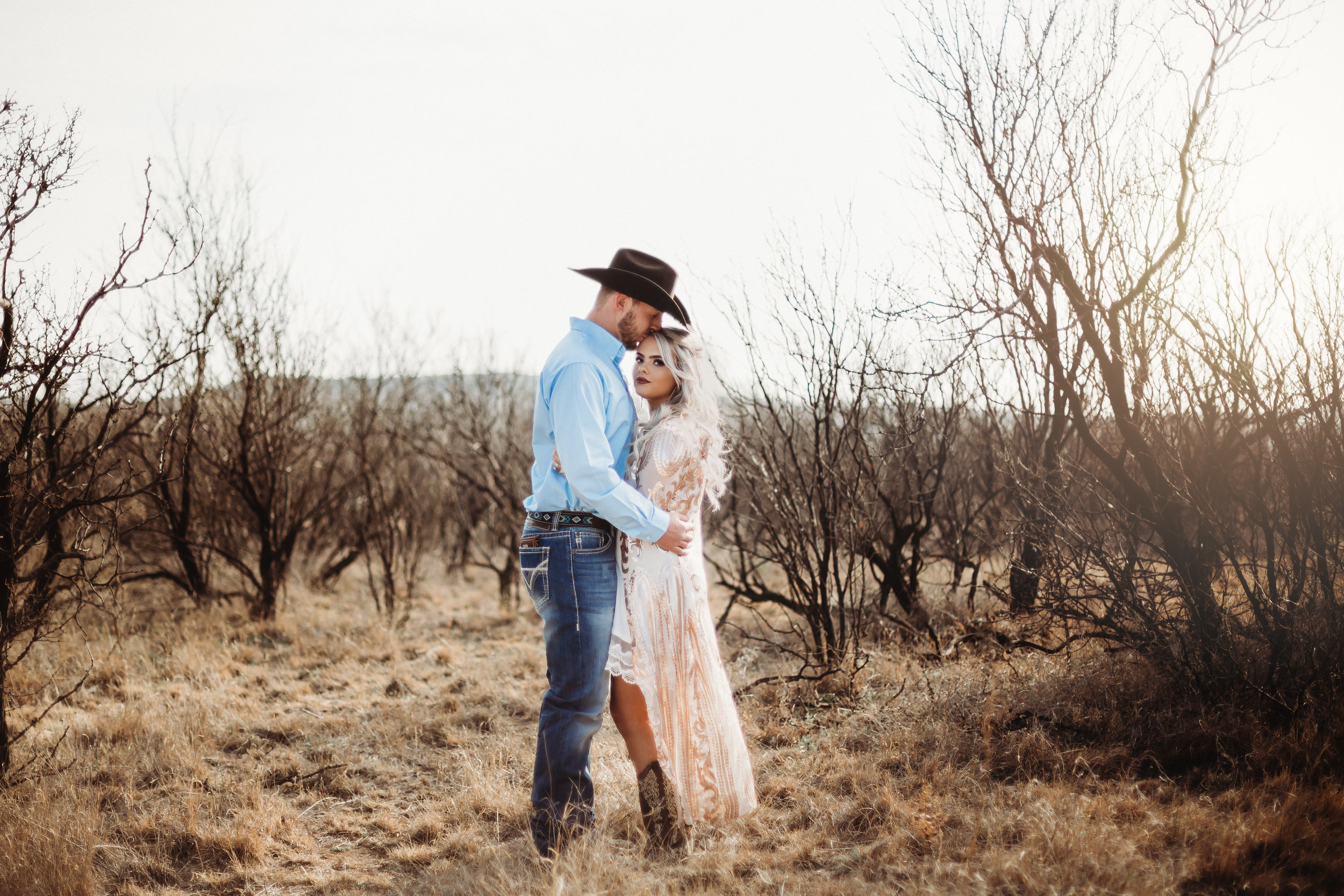 Engaged couple with kiss on the forehead cowboy hat sequins and cowboy boots with neutral background #engagementphotos #engaged #personality #amarillotexas #engagementphotographer #lifestylephotos #amarillophotographer #locationchoice #texasengagementphotos #engagment #tealawardphotography #westernstyle