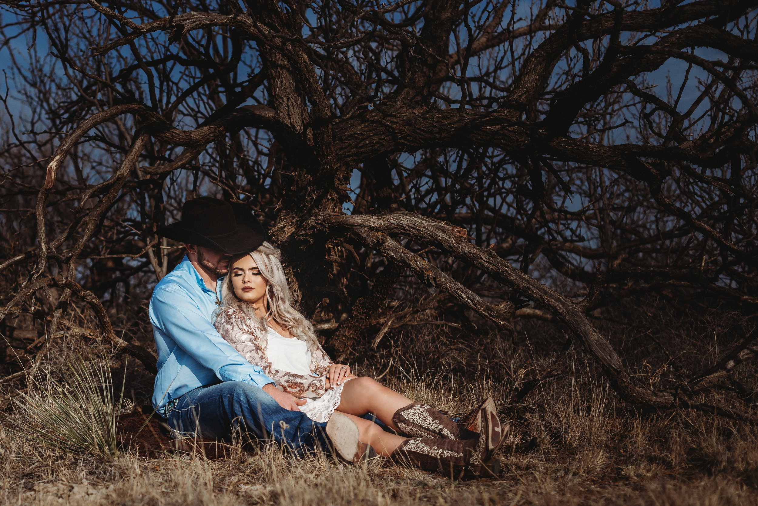 Distance shot of engaged couple sitting with bare trees behind them #engagementphotos #engaged #personality #amarillotexas #engagementphotographer #lifestylephotos #amarillophotographer #locationchoice #texasengagementphotos #engagment #tealawardphotography #westernstyle