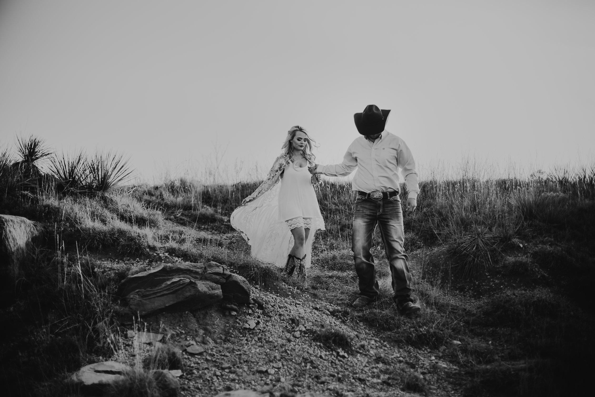 Groom to be leads his fiance down a path with photo in black and white #engagementphotos #engaged #personality #amarillotexas #engagementphotographer #lifestylephotos #amarillophotographer #locationchoice #texasengagementphotos #engagment #tealawardphotography #westernstyle