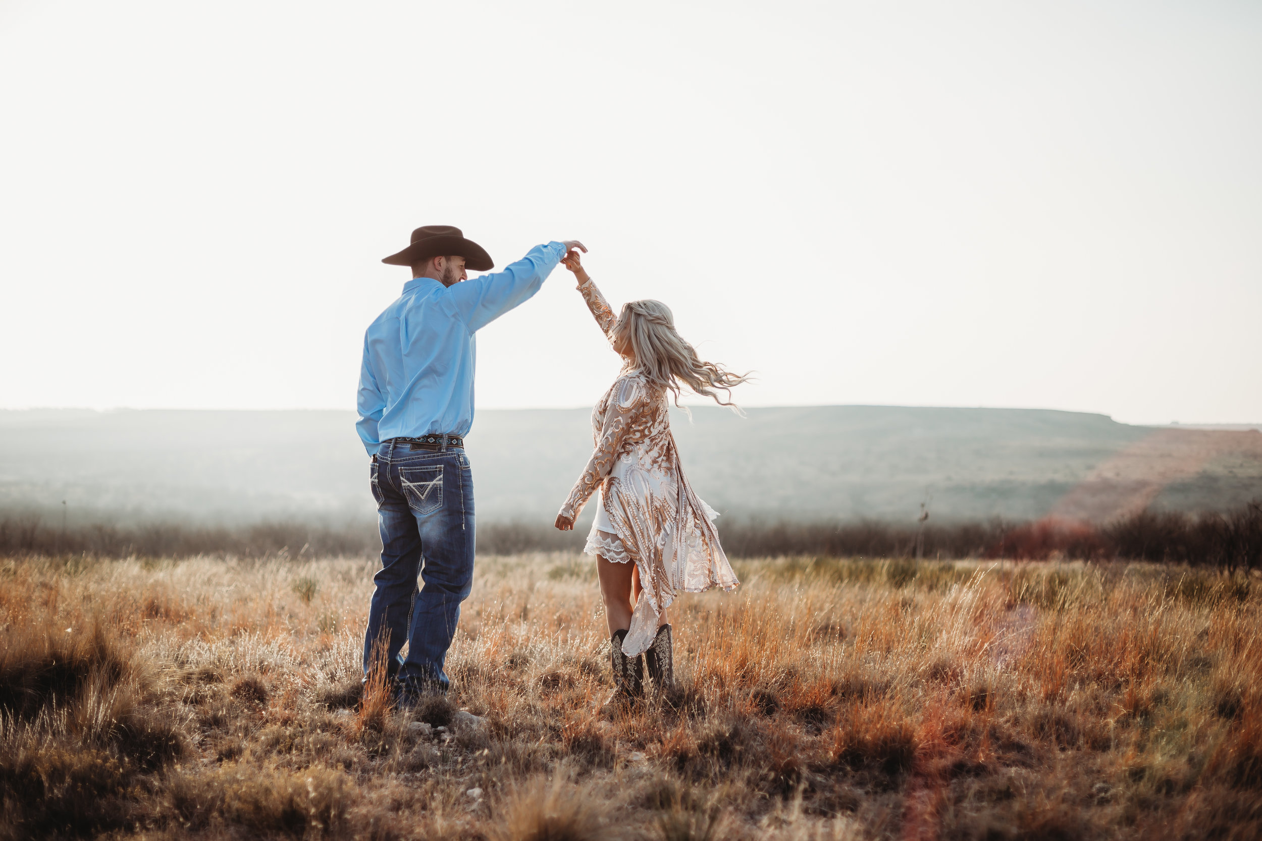 He spins her round and round on top of the world during engagement photo session #engagementphotos #engaged #personality #amarillotexas #engagementphotographer #lifestylephotos #amarillophotographer #locationchoice #texasengagementphotos #engagment #tealawardphotography #westernstyle