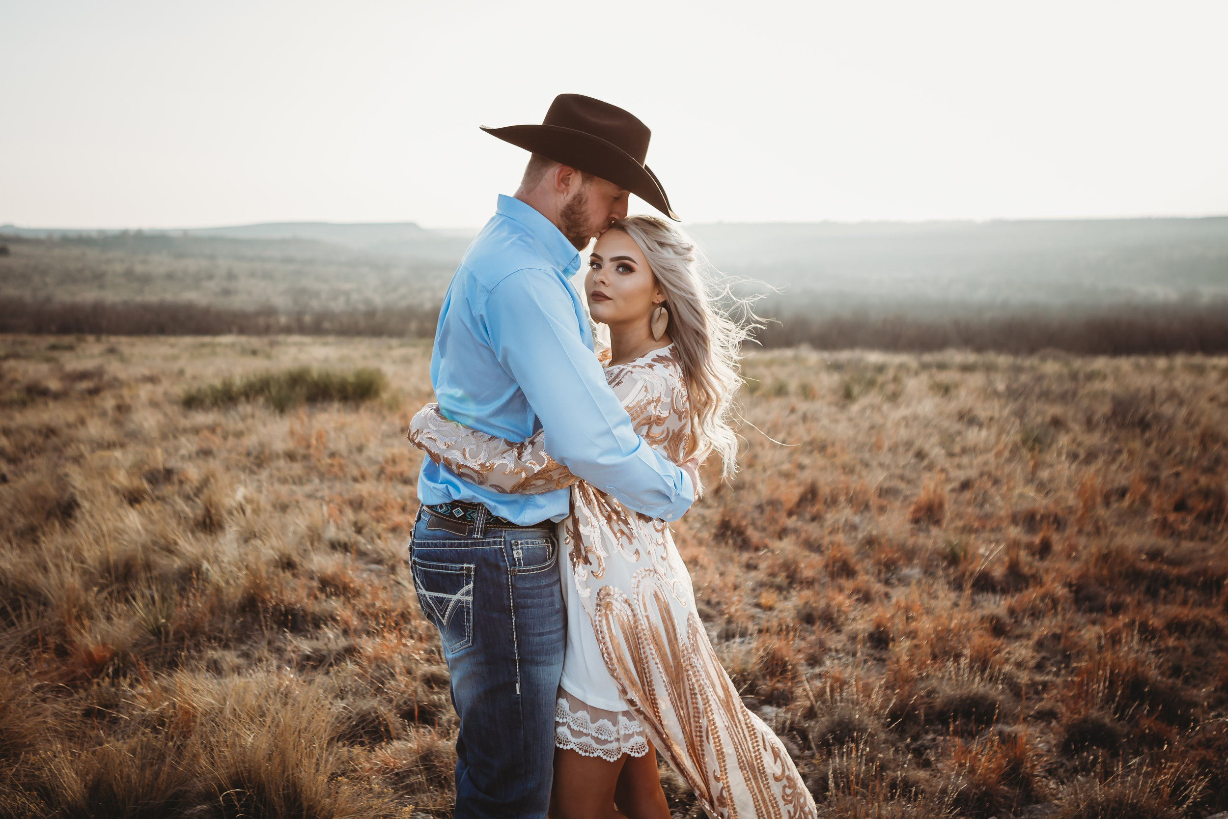 Profile of bride to be and groom to be kissing her on the forehead in the sun set #engagementphotos #engaged #personality #amarillotexas #engagementphotographer #lifestylephotos #amarillophotographer #locationchoice #texasengagementphotos #engagment #tealawardphotography #westernstyle