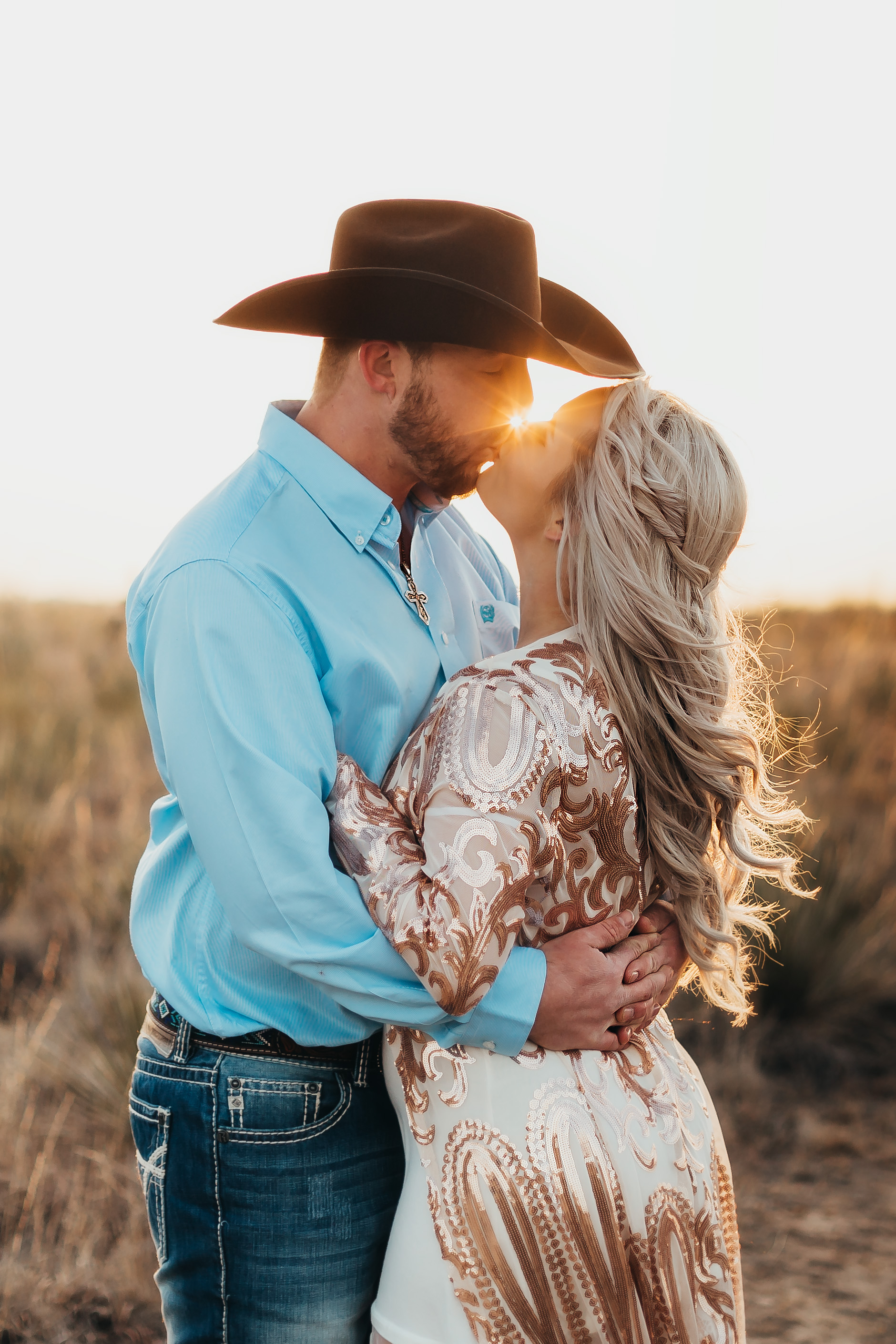 Sun set in the middle of an engagement kiss accenting wardrobe choices and cowboy hat #engagementphotos #engaged #personality #amarillotexas #engagementphotographer #lifestylephotos #amarillophotographer #locationchoice #texasengagementphotos #engagment #tealawardphotography #westernstyle