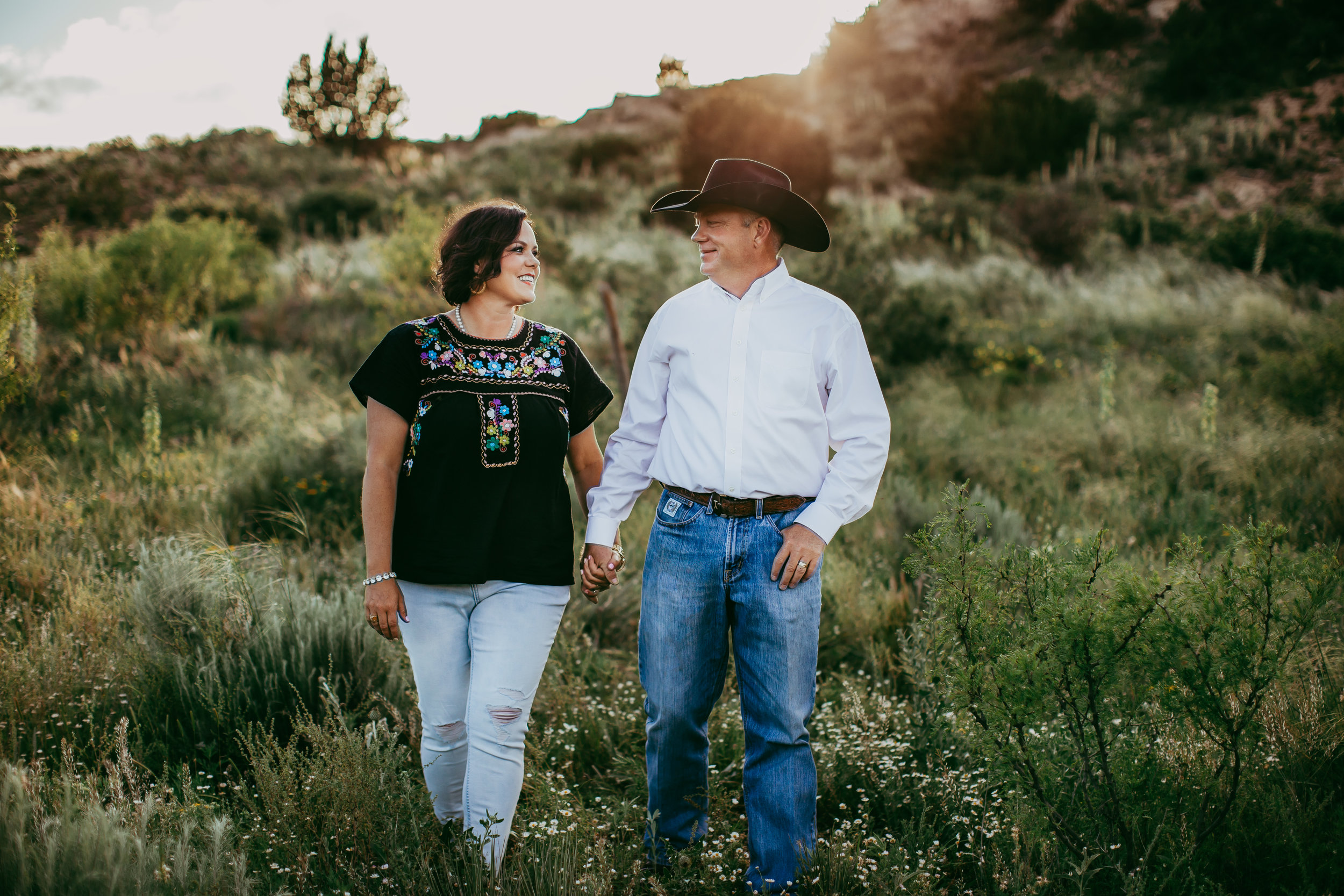 Mom and dad smiling at each other while walking through the pastures of their family ranch #tealawardphotography #texasfamilyphotographer #amarillophotographer #amarillofamilyphotographer #lifestylephotography #emotionalphotography #familyphotosoot #family #lovingsiblings #purejoy #familyphotos #familyphotographer #greatoutdoors
