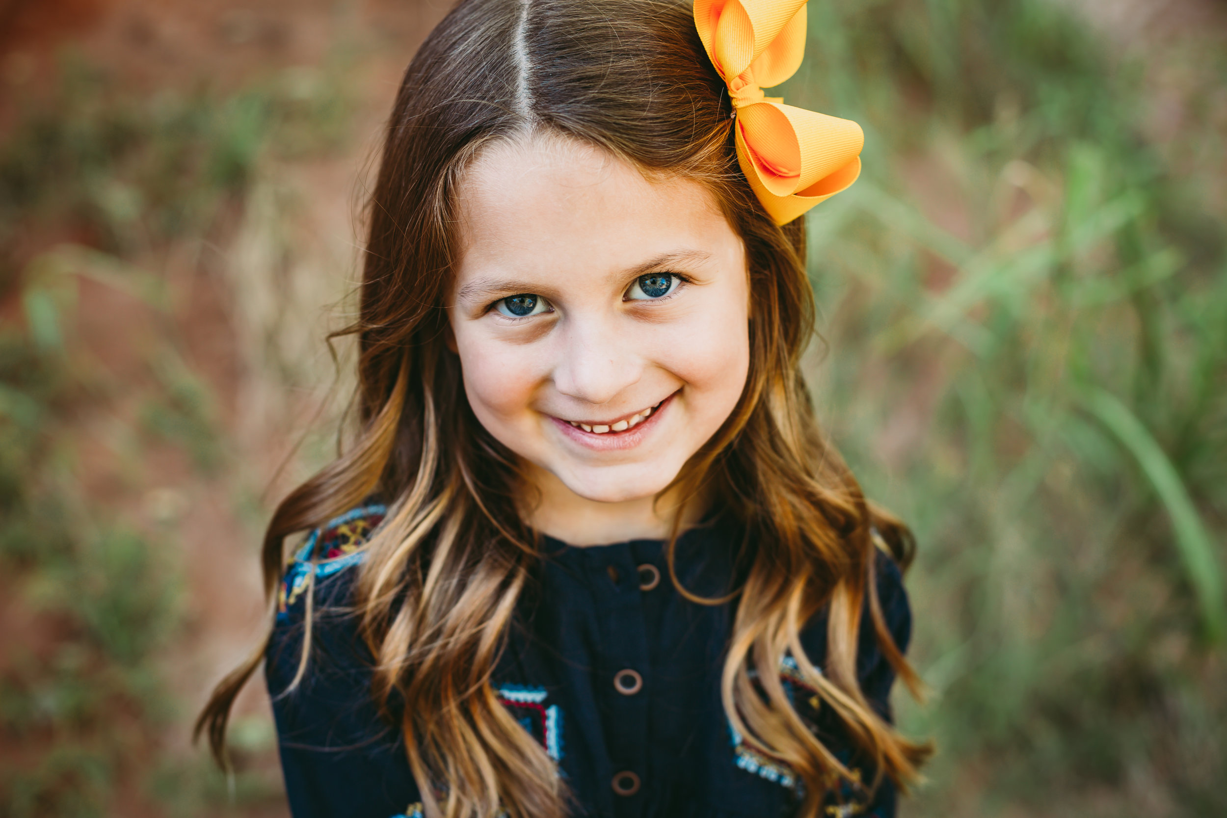 Solo photo of big sister with a large yellow bow in ther hair smiling at the camera #tealawardphotography #texasfamilyphotographer #amarillophotographer #amarillofamilyphotographer #lifestylephotography #emotionalphotography #familyphotosoot #family #lovingsiblings #purejoy #familyphotos #familyphotographer #greatoutdoors