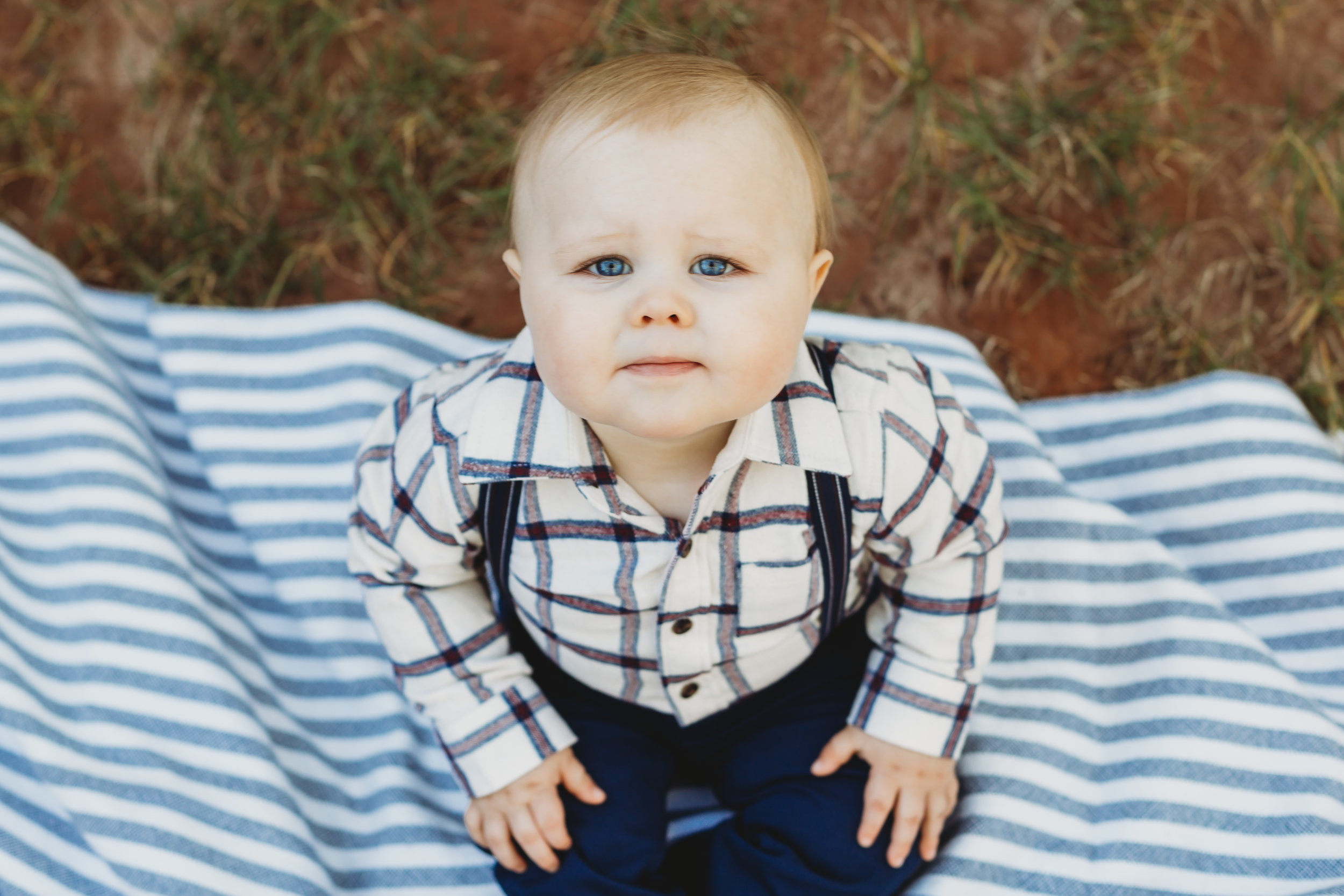 Baby brother sitting on picnic blanket looking up at the camera in stripes and suspenders #tealawardphotography #texasfamilyphotographer #amarillophotographer #amarillofamilyphotographer #lifestylephotography #emotionalphotography #familyphotosoot #family #lovingsiblings #purejoy #familyphotos #familyphotographer #greatoutdoors