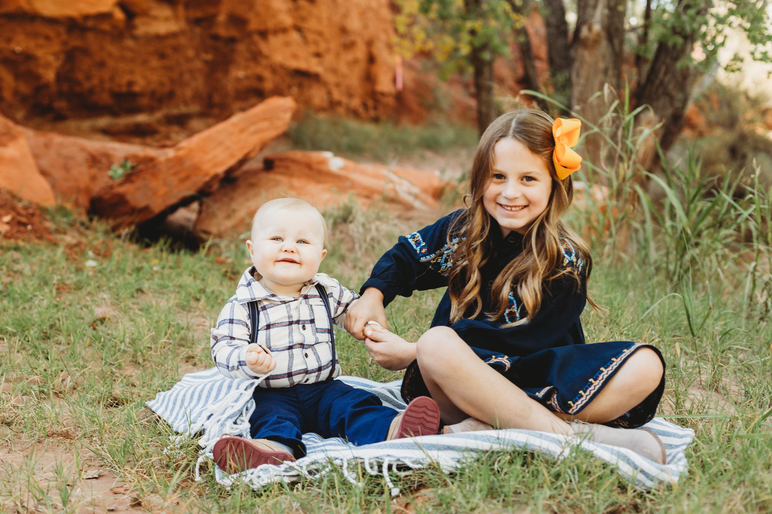 Brother and sister sitting on picnic blanket with greenery and red rock behind them smiling at the camera #tealawardphotography #texasfamilyphotographer #amarillophotographer #amarillofamilyphotographer #lifestylephotography #emotionalphotography #familyphotosoot #family #lovingsiblings #purejoy #familyphotos #familyphotographer #greatoutdoors