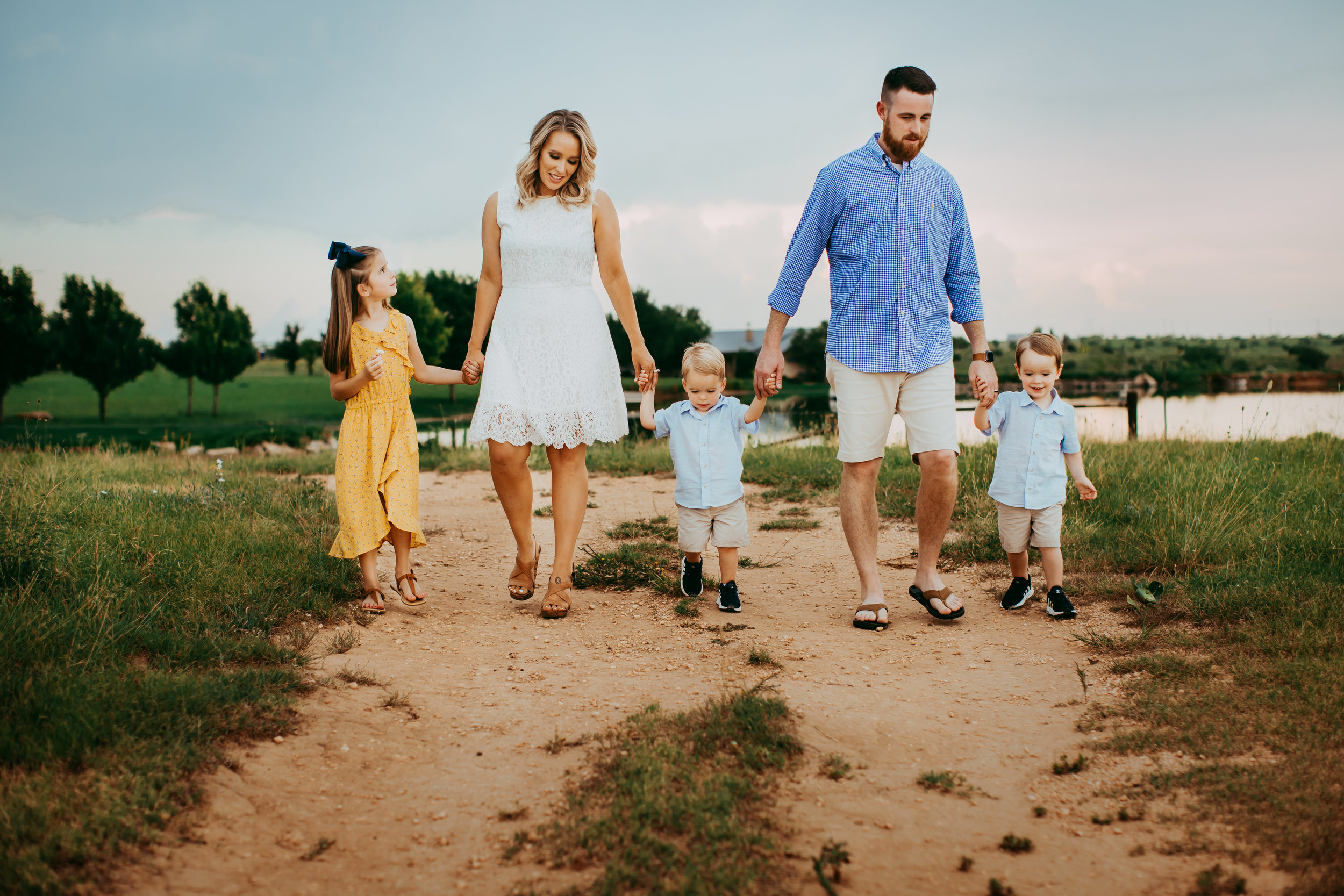 Family of five walking together down water side path #tealawardphotography #texasfamilyphotographer #amarillophotographer #amarillofamilyphotographer #lifestylephotography #emotionalphotography #familyphotosoot #family #lovingsiblings #purejoy #familyphotos #familyphotographer #greatoutdoors #naturalfamilyinteraction