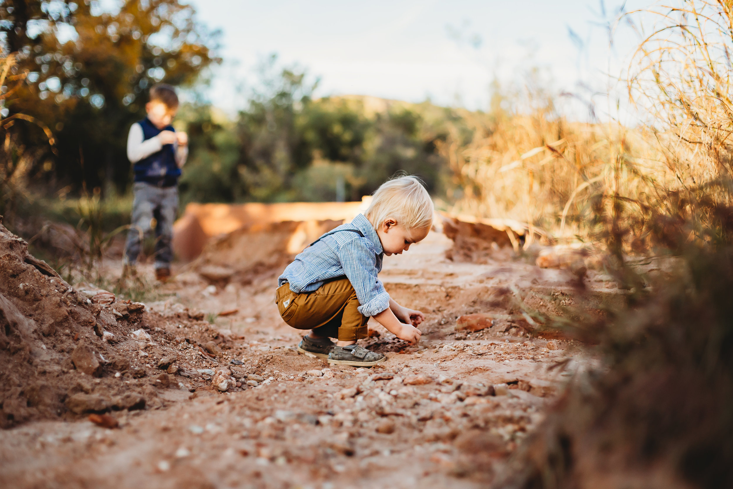 Focus on boy playing with rocks and brother in the background #tealawardphotography #texaslocationchoice #amarillophotographer #amarillofamilyphotographer #emotionalphotography #engagementphotography #couplesphotography #pickingaphotosessionlocation #whatsimportant #everythingtogether #pickingcolorsforphotos #location #photosessionlocation