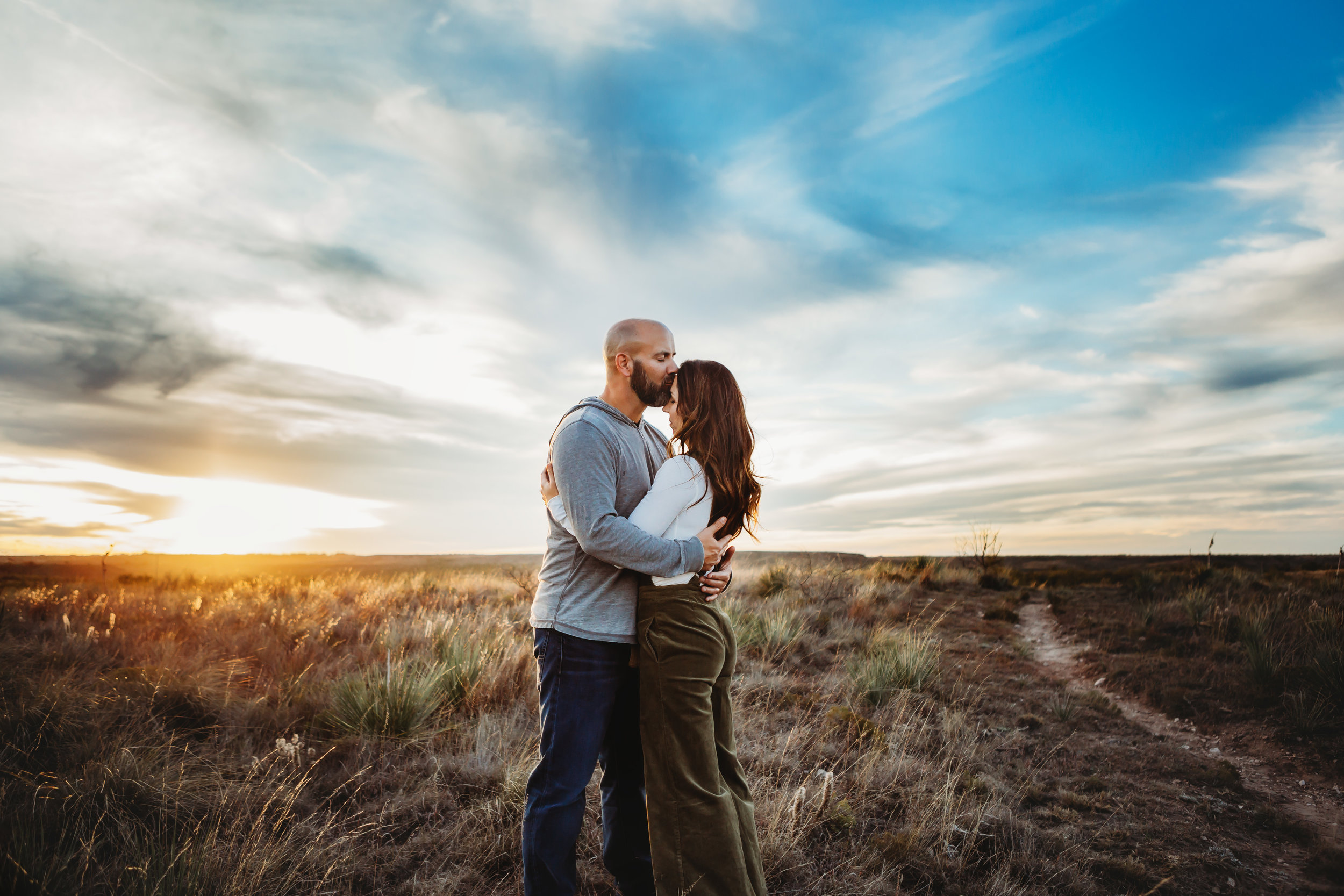 Wide open space behind couple with a kiss on the forehead #tealawardphotography #texaslocationchoice #amarillophotographer #amarillofamilyphotographer #emotionalphotography #engagementphotography #couplesphotography #pickingaphotosessionlocation #whatsimportant #everythingtogether #pickingcolorsforphotos #location #photosessionlocation