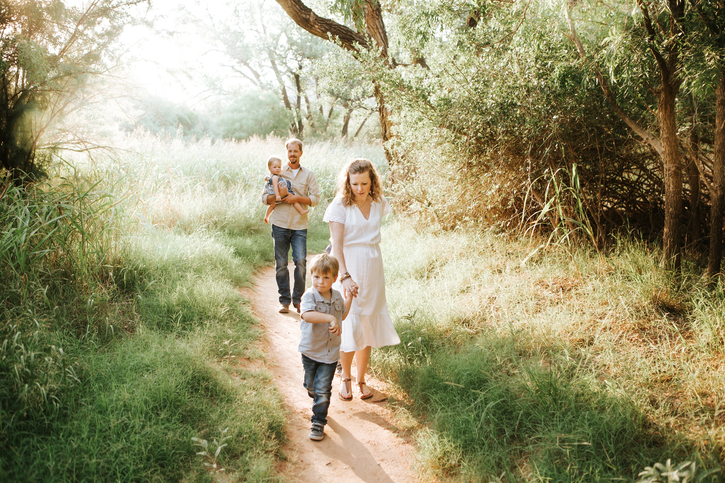 Family walking down the path with sun set behind them and green lush grass surrounding them #tealawardphotography #texassummerphotographer #pictureseason #amarillophotographer #amarillofamilyphotographer #emotionalphotography #engagementphotography #couplesphotography #pickingaseasonforphotosessions #whatsimportant #everythingtogether #pickingcolorsforphotos #summerphotos #greeneryinphotos