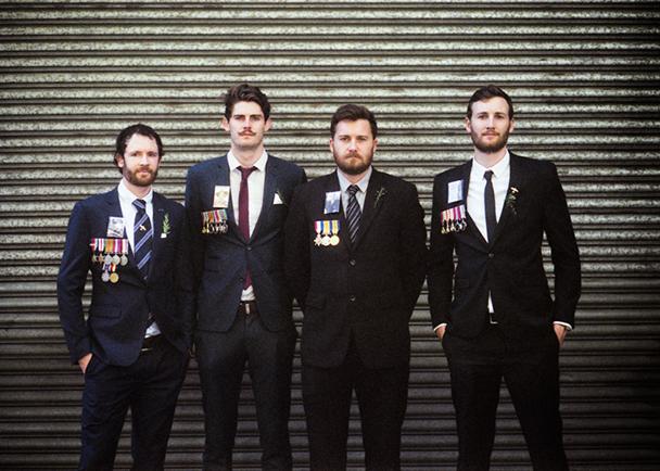 Bryan, Adam, Robert and Michael Cook bearing photographs of Brian Fallon, Mervyan Cook, Lloyd Cook and William Brew