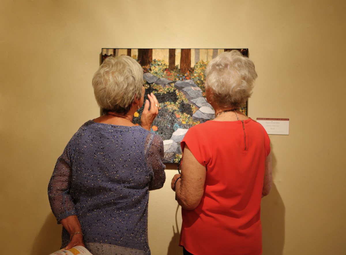 """Visitors admire the textile art by Denise Oyama Miller, """"Yosemite Reflections"""""""