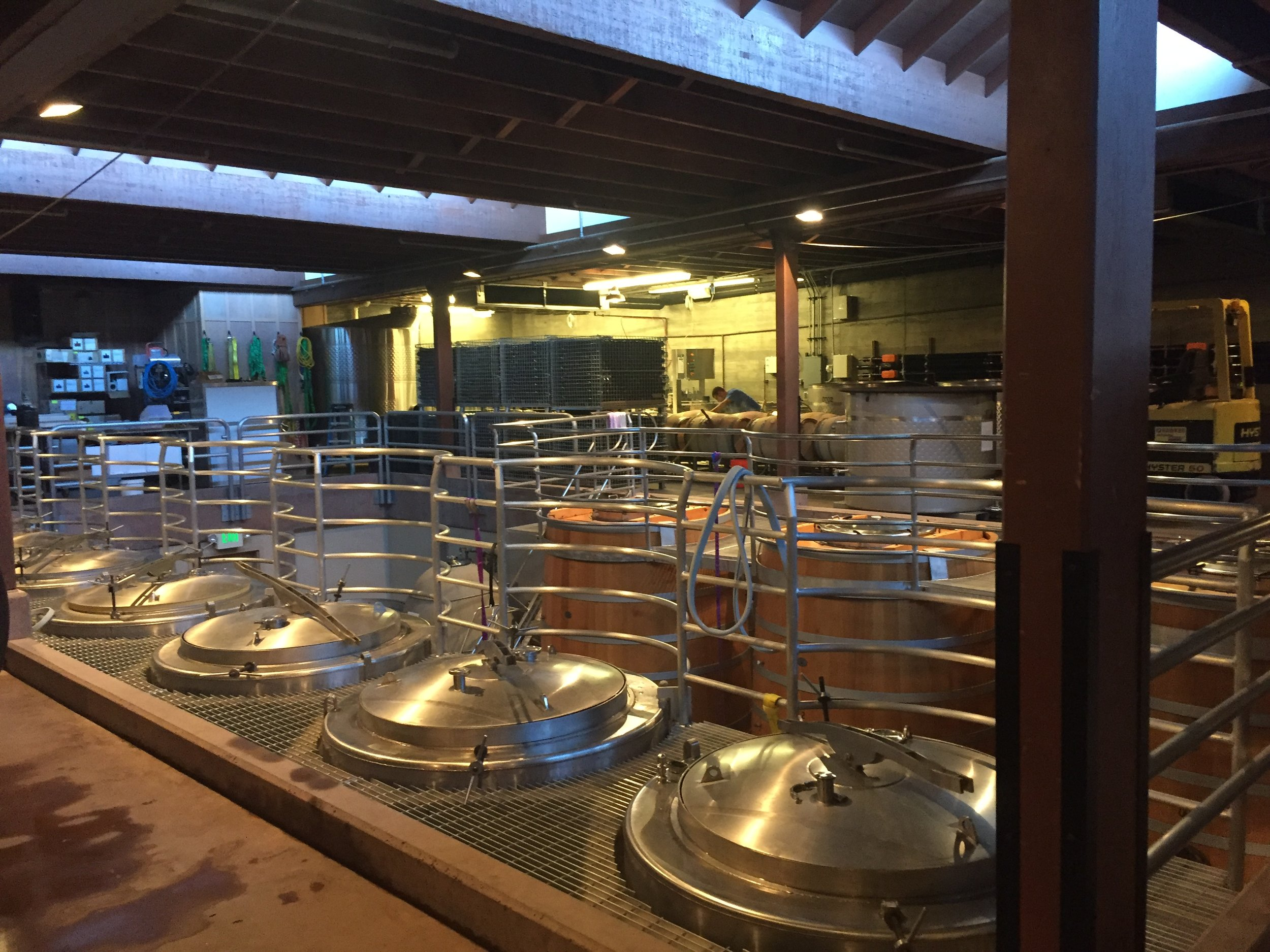 Large stainless steel fermentation tanks in action during crush and production.
