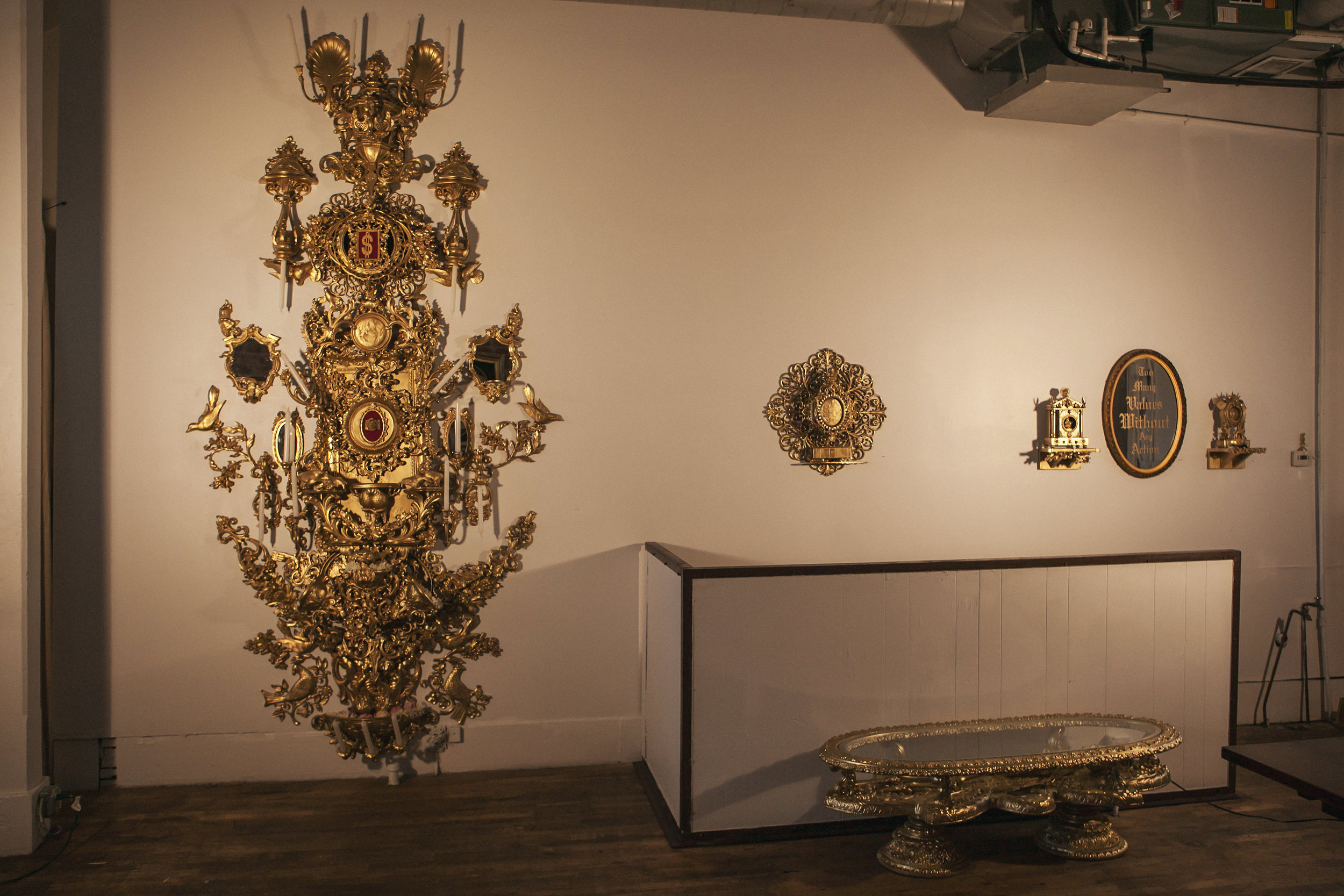 """Gallery view.  """"The Symbolic Collisions of a Tragicomic Character Worth His Weight in Gold"""" (left)  """"People Transport"""" (center)  """"Mini Mantle from North Mexico #1 & #2"""" """"Too Many Values Without Any Action"""" (right)  """"Cartel Victim Catacomb"""" (below)"""