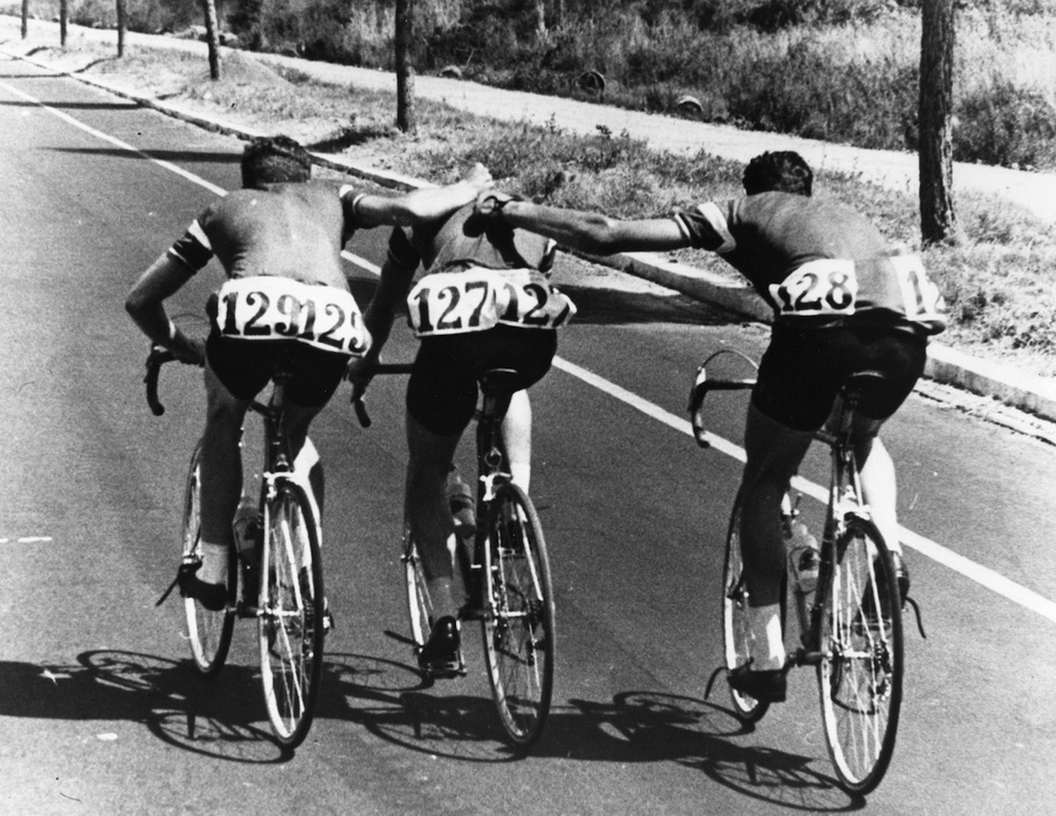 Denmark's Knud Jensen (middle) being escorted by two teammates during the Rome Olympics. He would collapse and die shortly after this photo. This event is a focal point in Mark Johnson's book,  Spitting in the Soup . (photo is not mine)