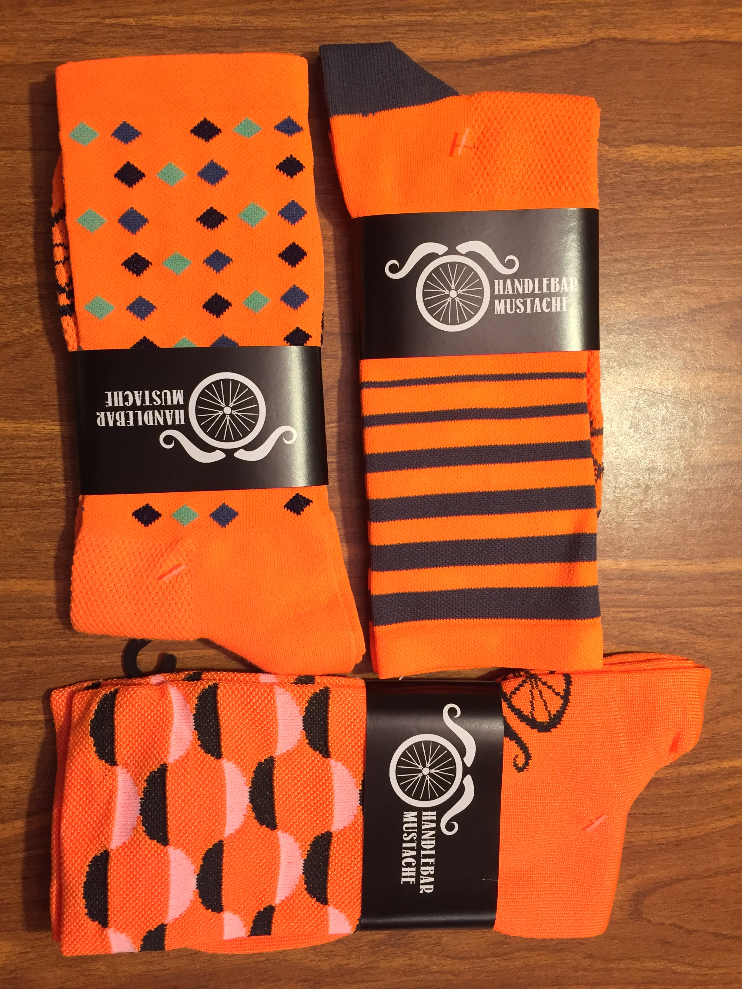 Two sets of socks across the top and a set of Belgian booties across the bottom by Handlebar Mustache. The orange goes perfectly with the team kit.