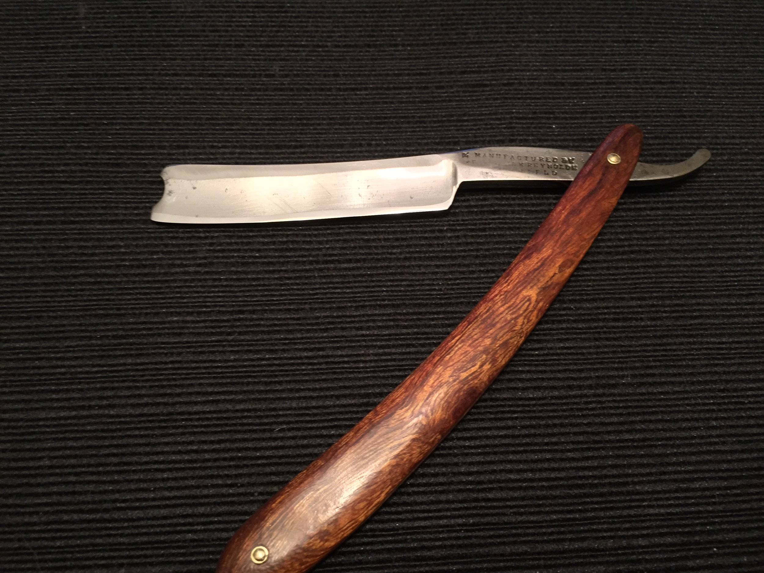 The Frederick Reynolds near wedge straight razor with barber's notch as it came out of the box from Portland Razor Company.