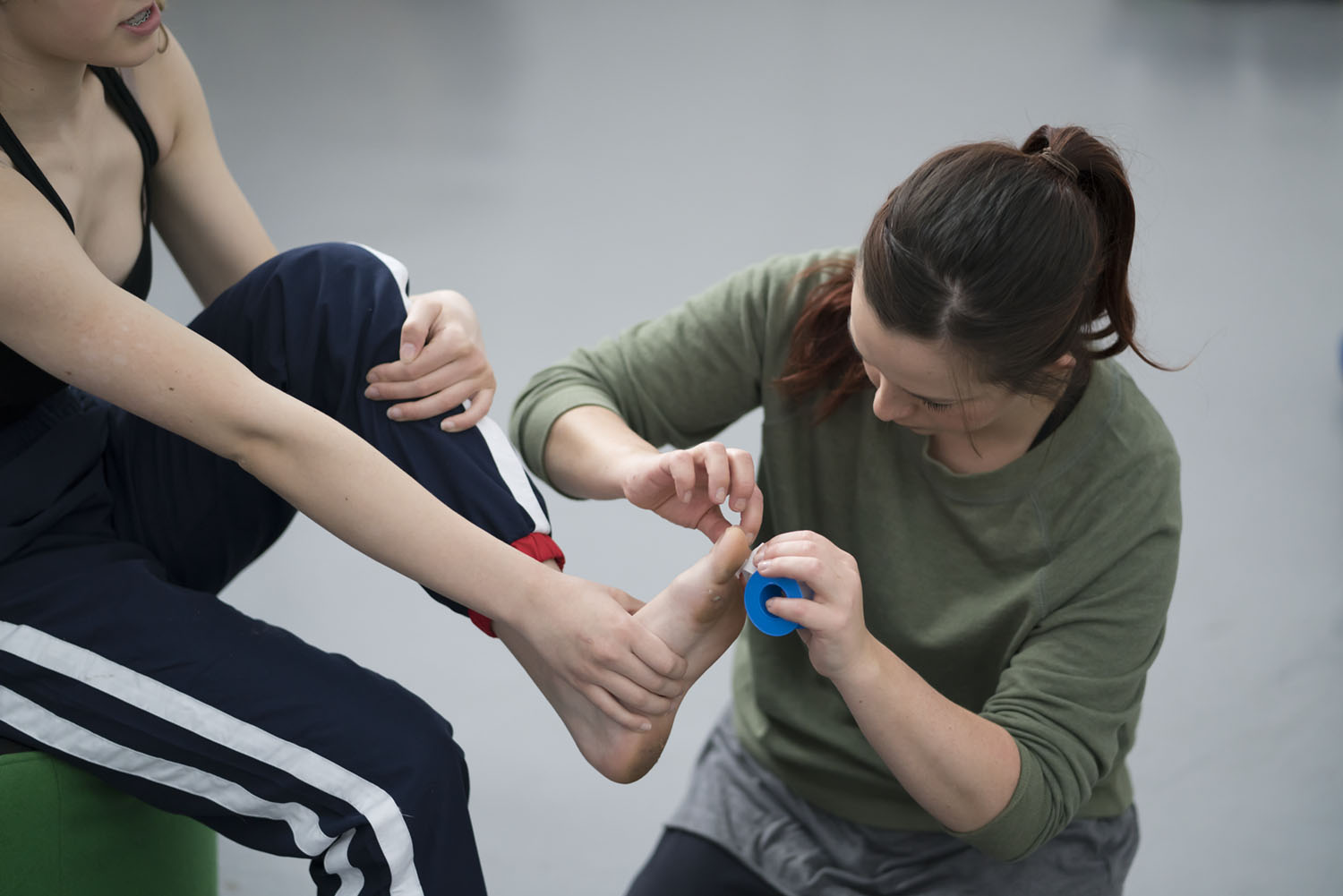 Trainee Imogen helps a dancer patch up before going on stage