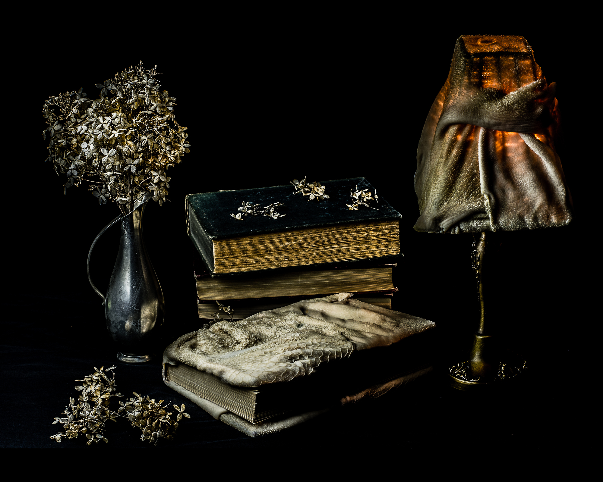 Book bound in sheep stomach with dead flowers and sheep stomach lampshade.