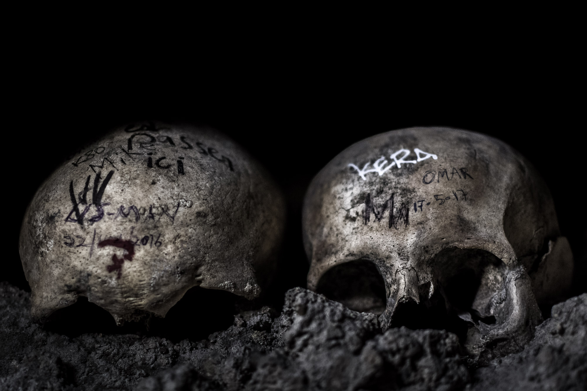 A pair of skulls, marked with graffiti, in the Catacombs of Paris.