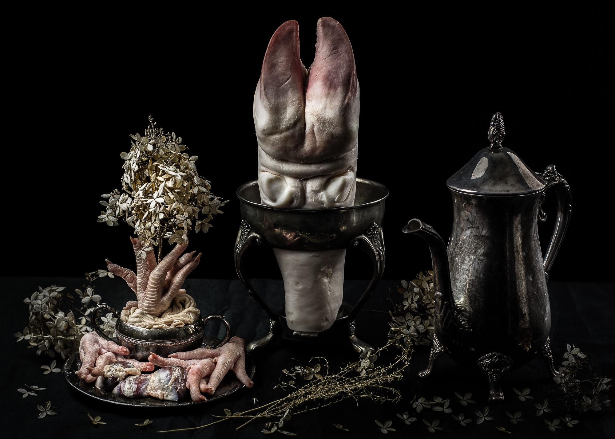 Still life arrangement of cow foot, chicken feet, duck gizzards, pig intestines, dead flowers, and tea set.
