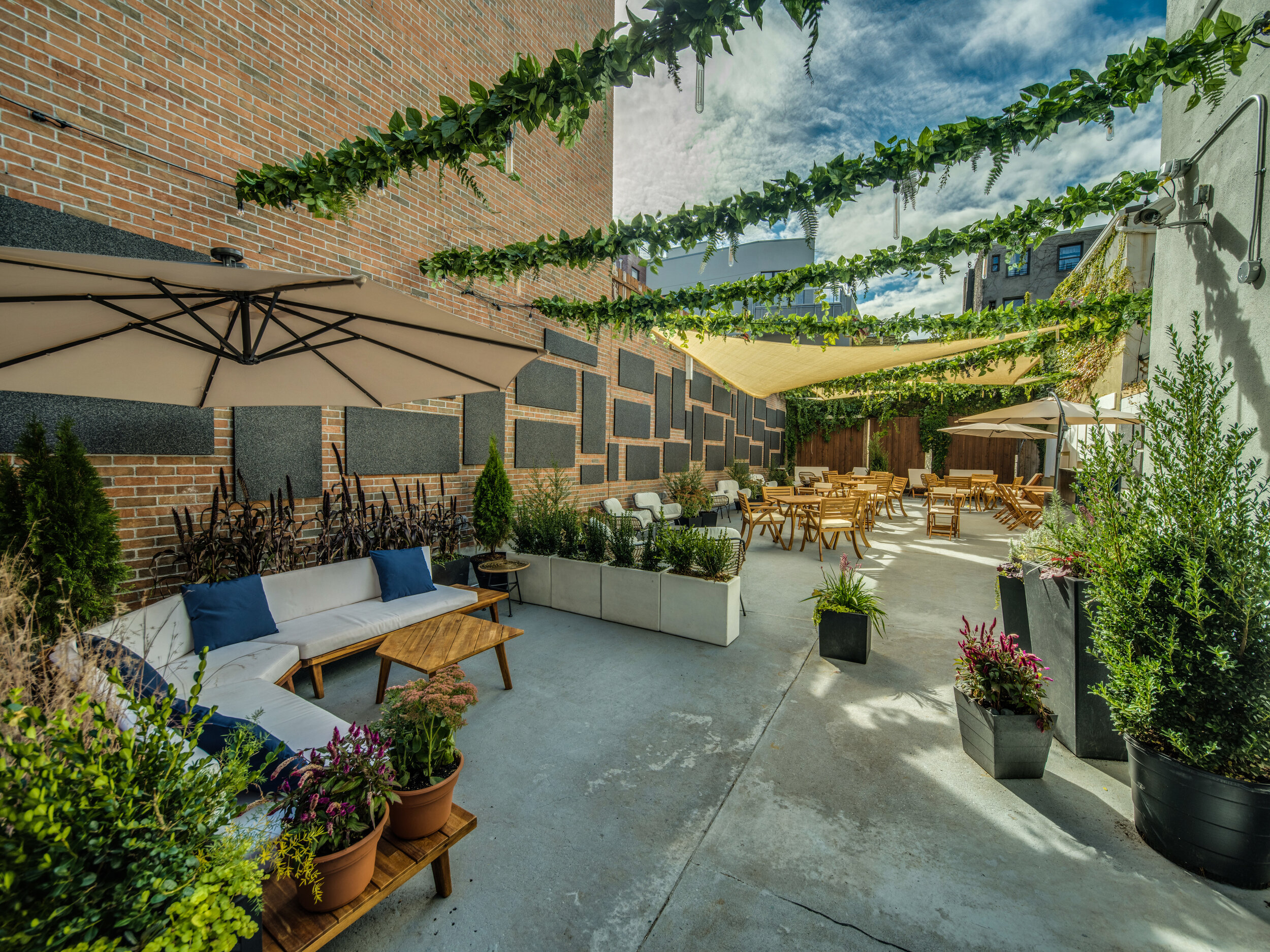 Sun-drenched outdoor patio with ample seating and a relaxed ambiance. Photo Credit - Oleg March