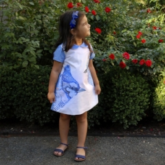 "A-DRESS FEATHER-DO $95.00    Dress with cap sleeve, side pocket, back buttons & adjustable belt. Original artwork on fabric and includes a mini-storybook ""Bird Hairdo"""