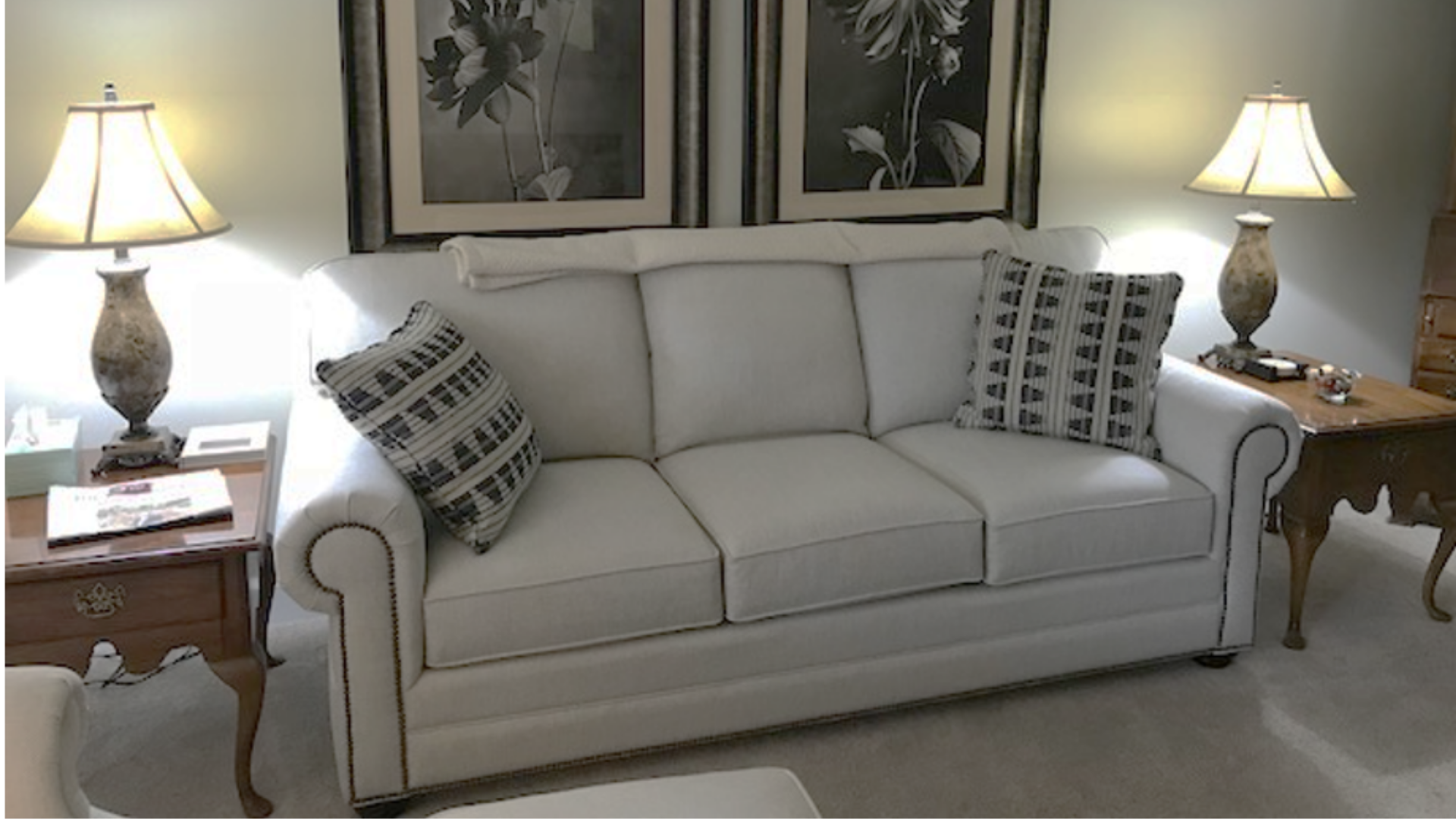 Traditional white sofa with panel arm in revolution fabric with antique brass nail trim transitional pillows | Michael Helwig Interiors|