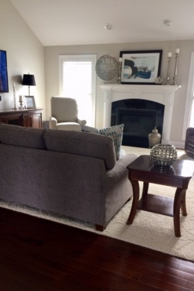 Modern styled fireplace mantle with gray transitional sofa and espresso transitional end tables | Michael Helwig Interiors |