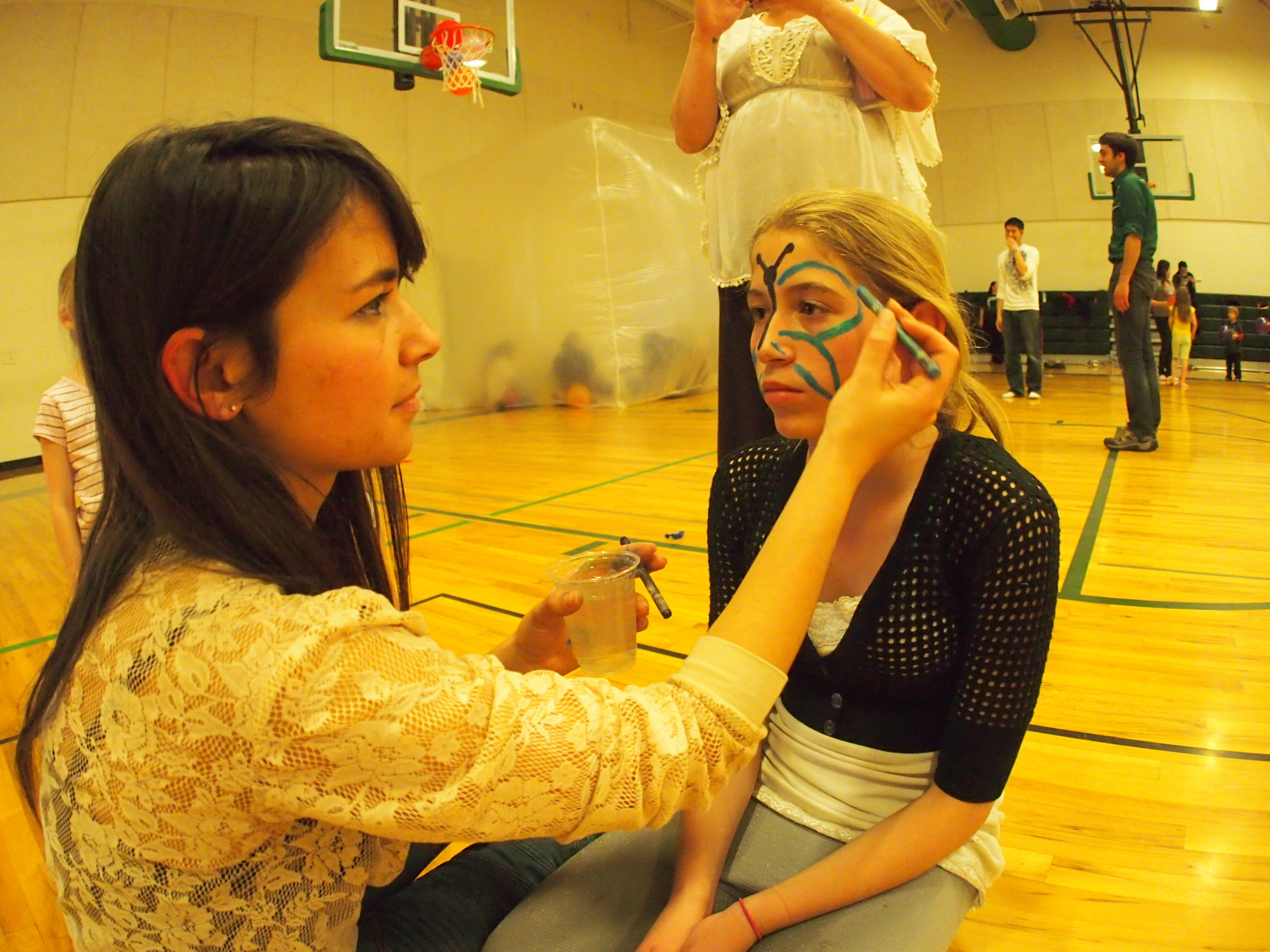 Artist and AmeriCorps VISTA Ashley Ross face-painting at the event.
