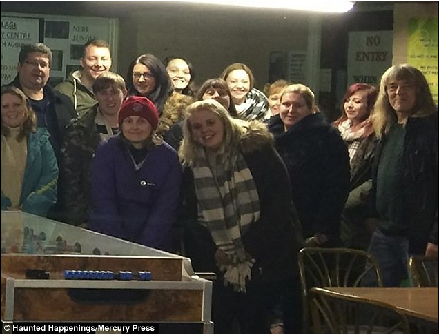 Miss Morritt, pictured centre in the striped scarf, said she also captured a chilling child's scream on her video of the grade-II listed building, known as The Village. She is pictured with her fellow ghost hunters.