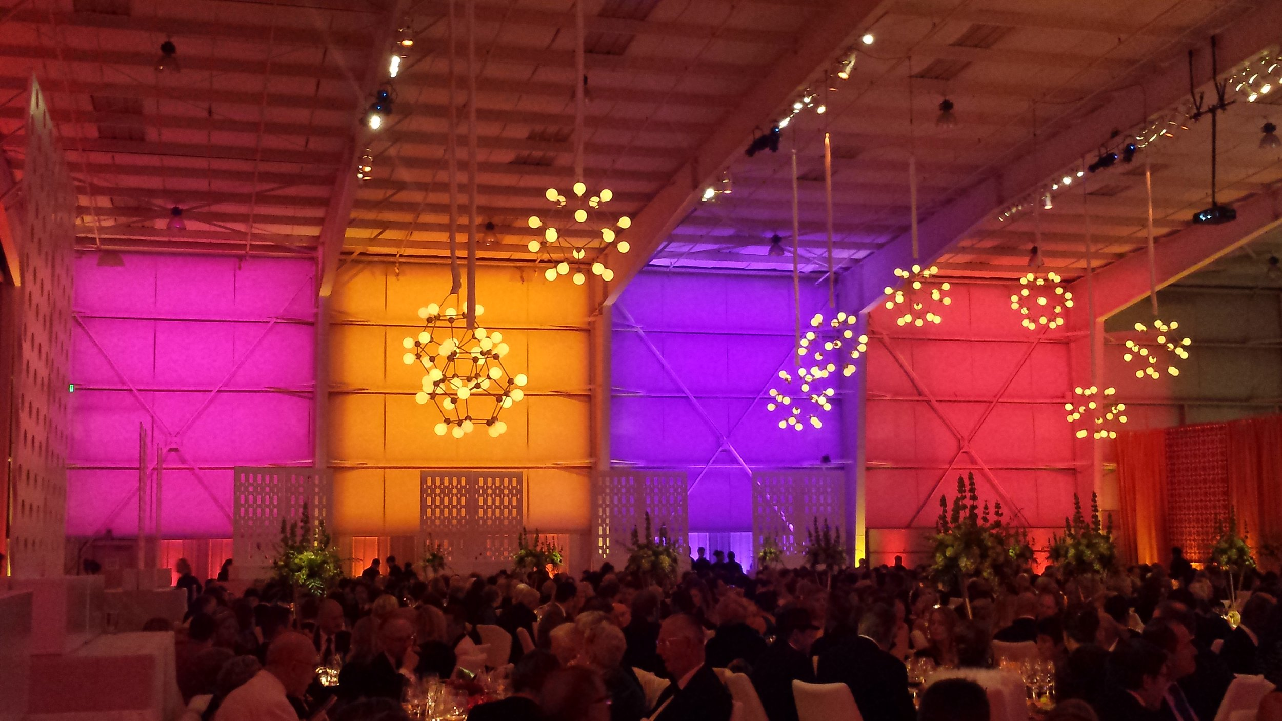 This airplane hangar is transformed into a festive party through the use of color and light.