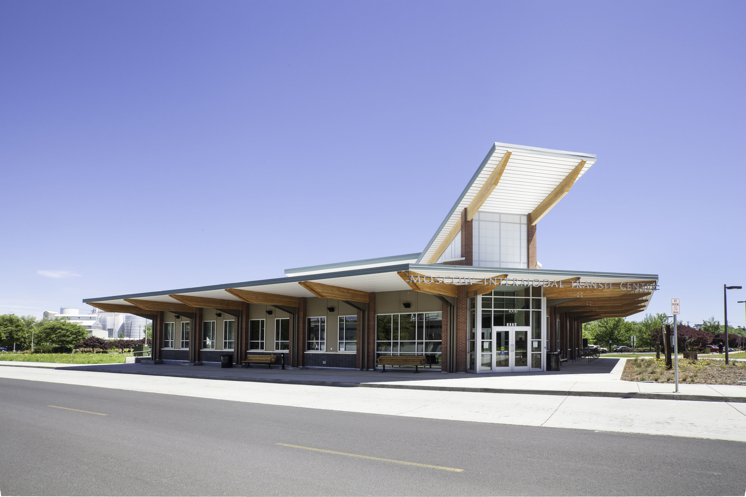 Owner: City of Moscow Location: Moscow, ID   The Moscow Intermodal Transit Center houses multiple local and regional transit tenants and provides a convenient central operating location. The design focuses public space toward the street with the main service lobby adjacent and visually connected to the loading platforms and public plaza space. The standing seam metal roof, brick masonry, and exposed heavy timber wood materials are durable and fit with existing community context while glass, metal, and translucent panels set the building apart.