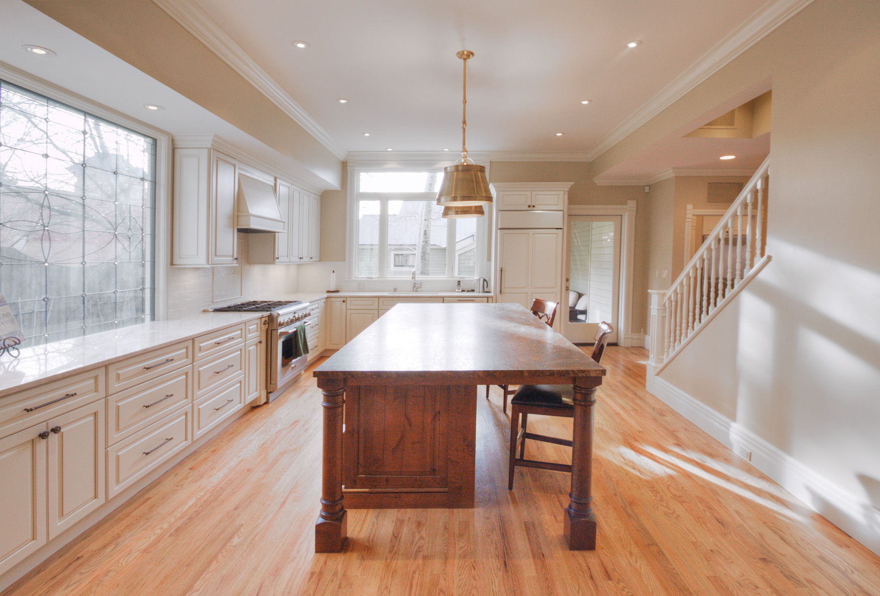 Open floor plan tan kitchen with large wood island