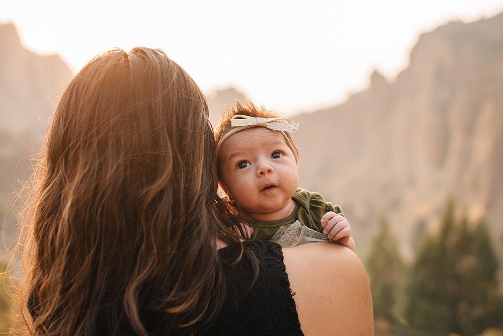 newborn baby girl peeks over her mon's shoulder