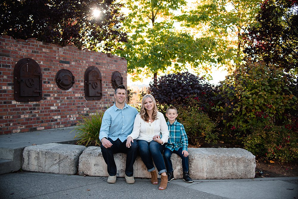 family of three poses by sitting on a brick wall in the Old Mill District in Bend.