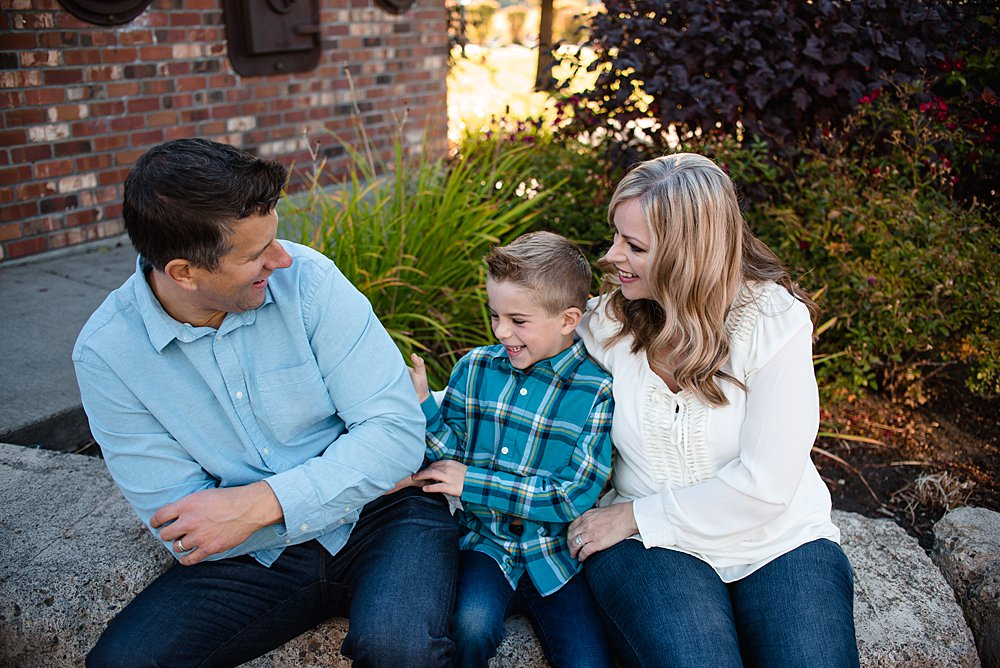 mom and dad sit by a brick wall in Bend, Oregon while tickling their son