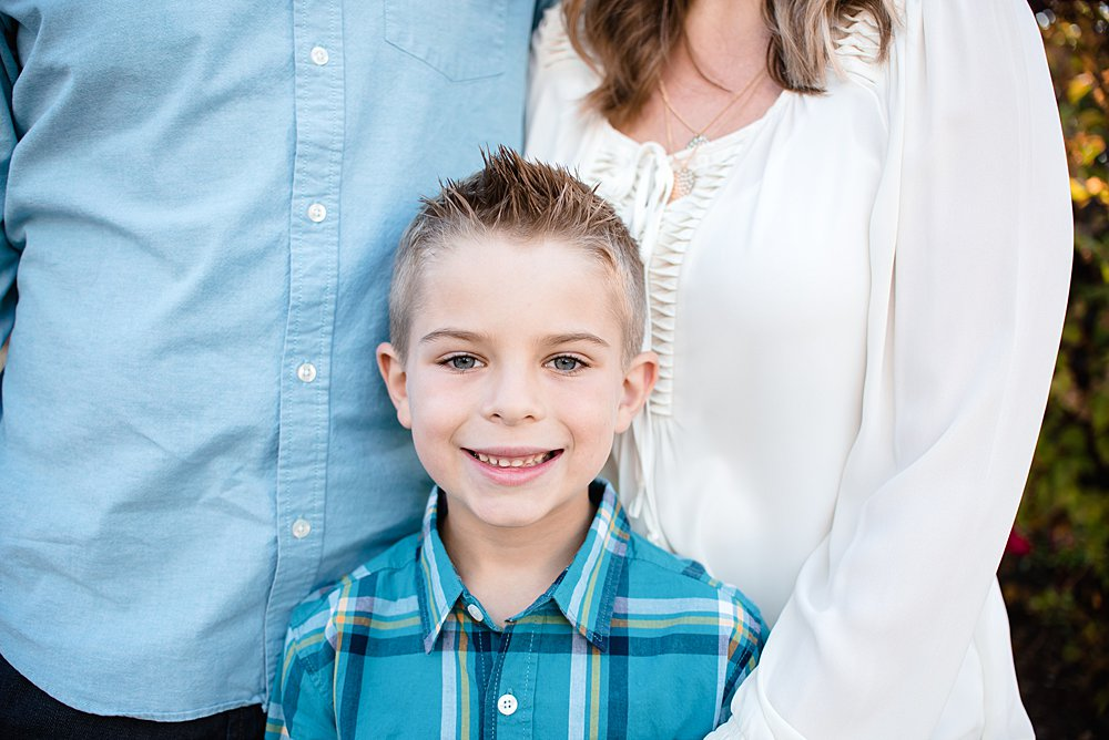 Close up of a boy looking at the camera while his family poses for a photo in the Old Mill District