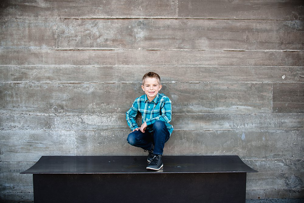 Boy poses while squatting on a bench in front of the shops at the Old Mill District in Bend Oregon