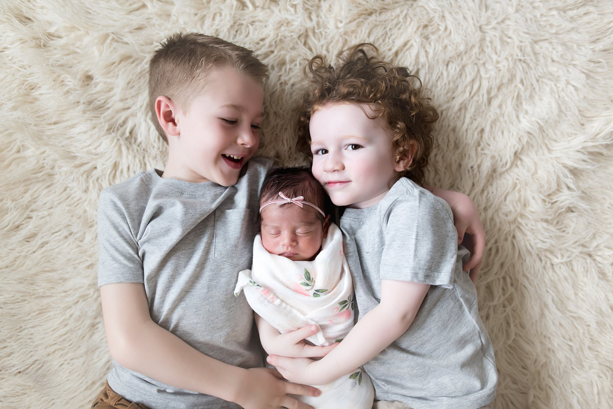brothers lay together with their new baby sister between them