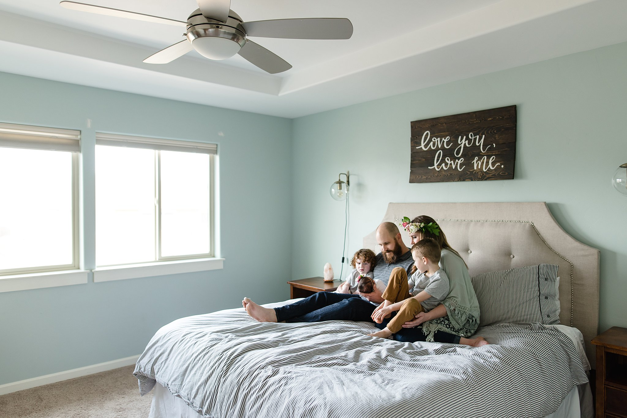 a peek through the doorway of a family snuggling together on the bed.