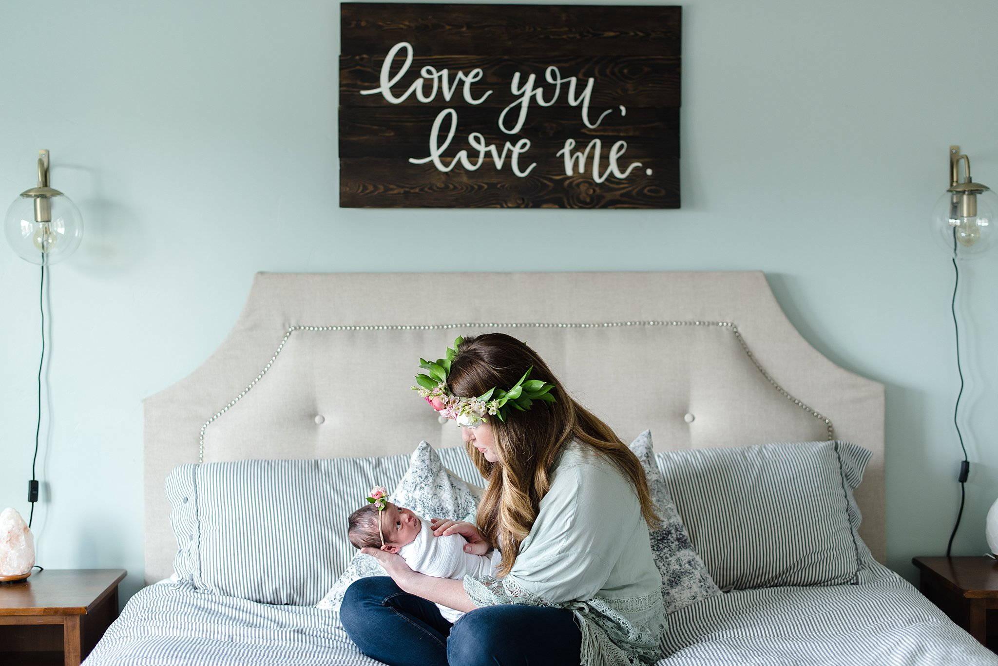 mom holds her baby girl on the bed