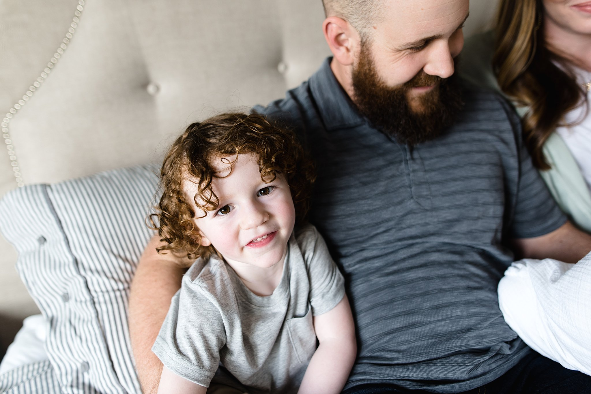 a boy looks up at the camera snuggled next to his dad
