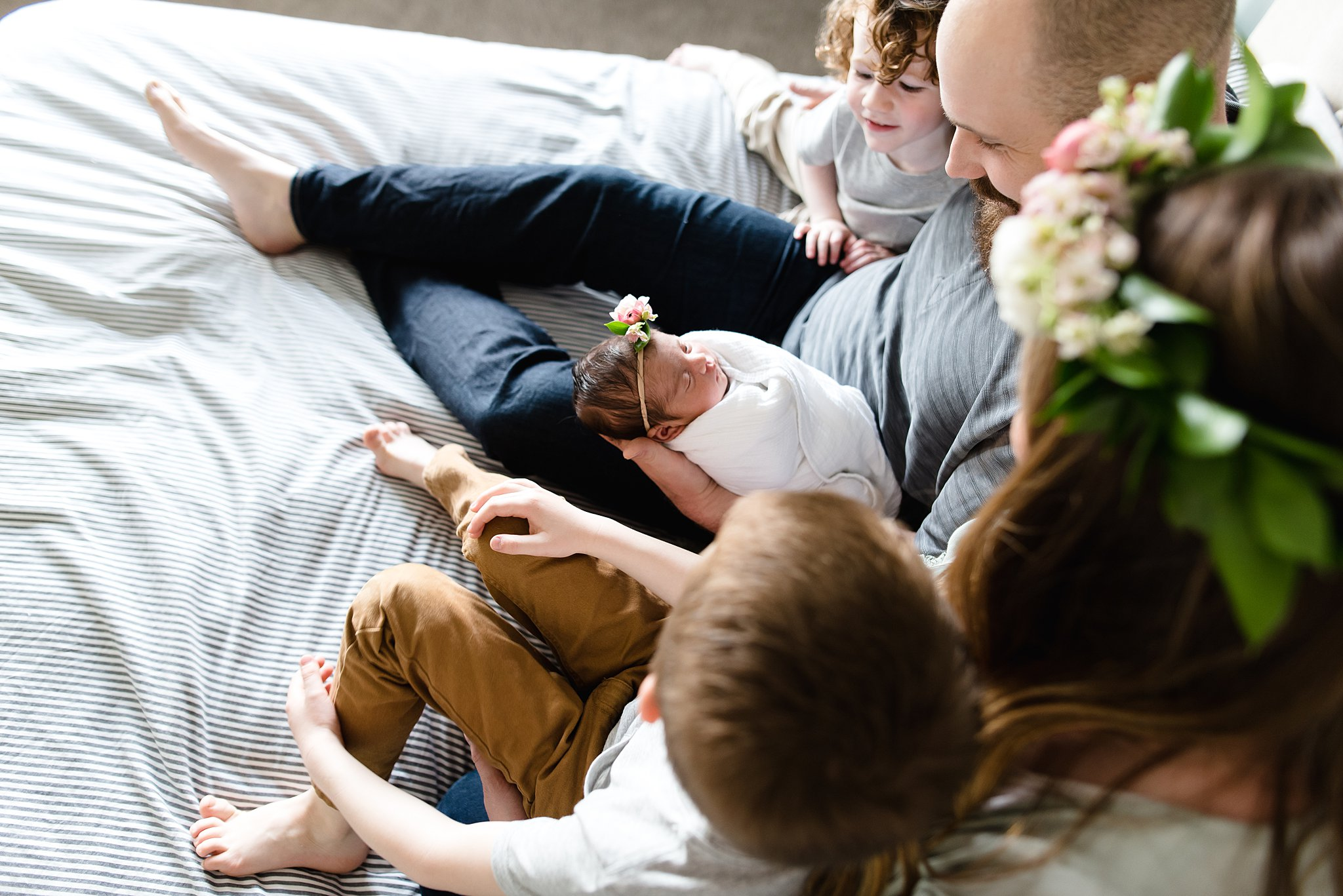 family is cozy together on a bed gazing adoringly at their new baby girl